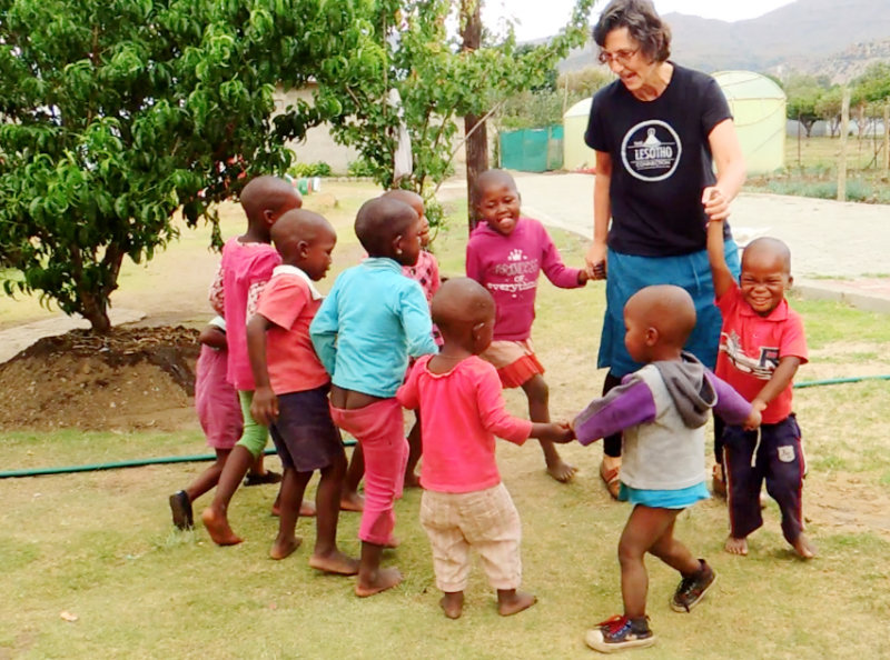 TLC volunteer Dr. Margie Wenz playing with kids at the Centre.