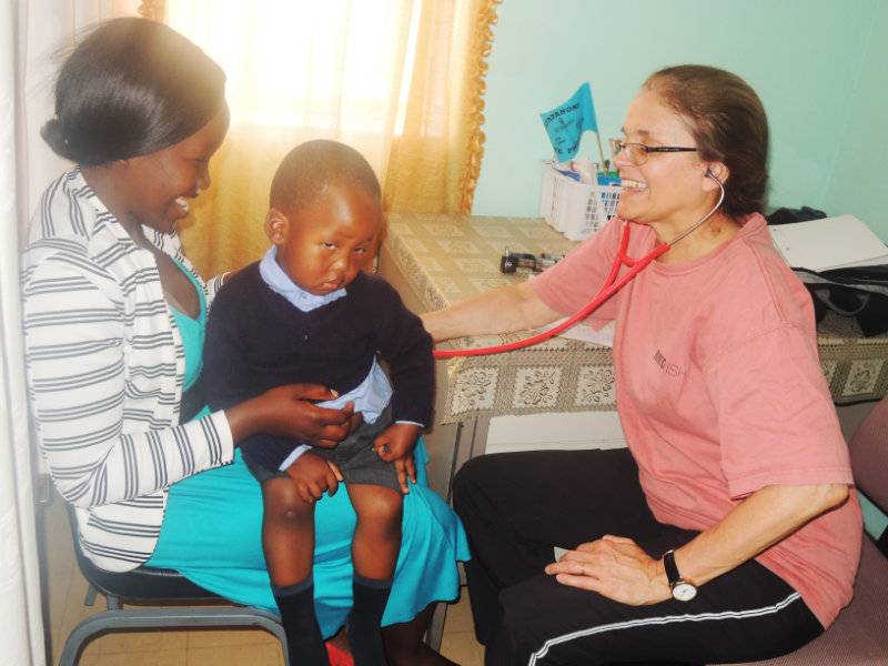 TLC volunteer Dr. Ann Failinger checking children at a local clinic.