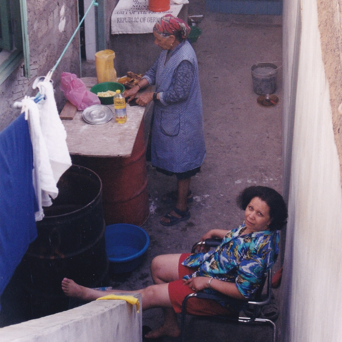 Joanna sits with her mother who is preparing a meal in Cruzinha, Cape Verde in 1992.