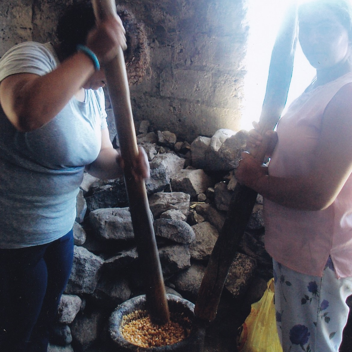 Margarida works with her cousin to grind cornmeal for cachupa with the pilon (pestle and mortar) in Cruzinha, Cape Verde in 2009.