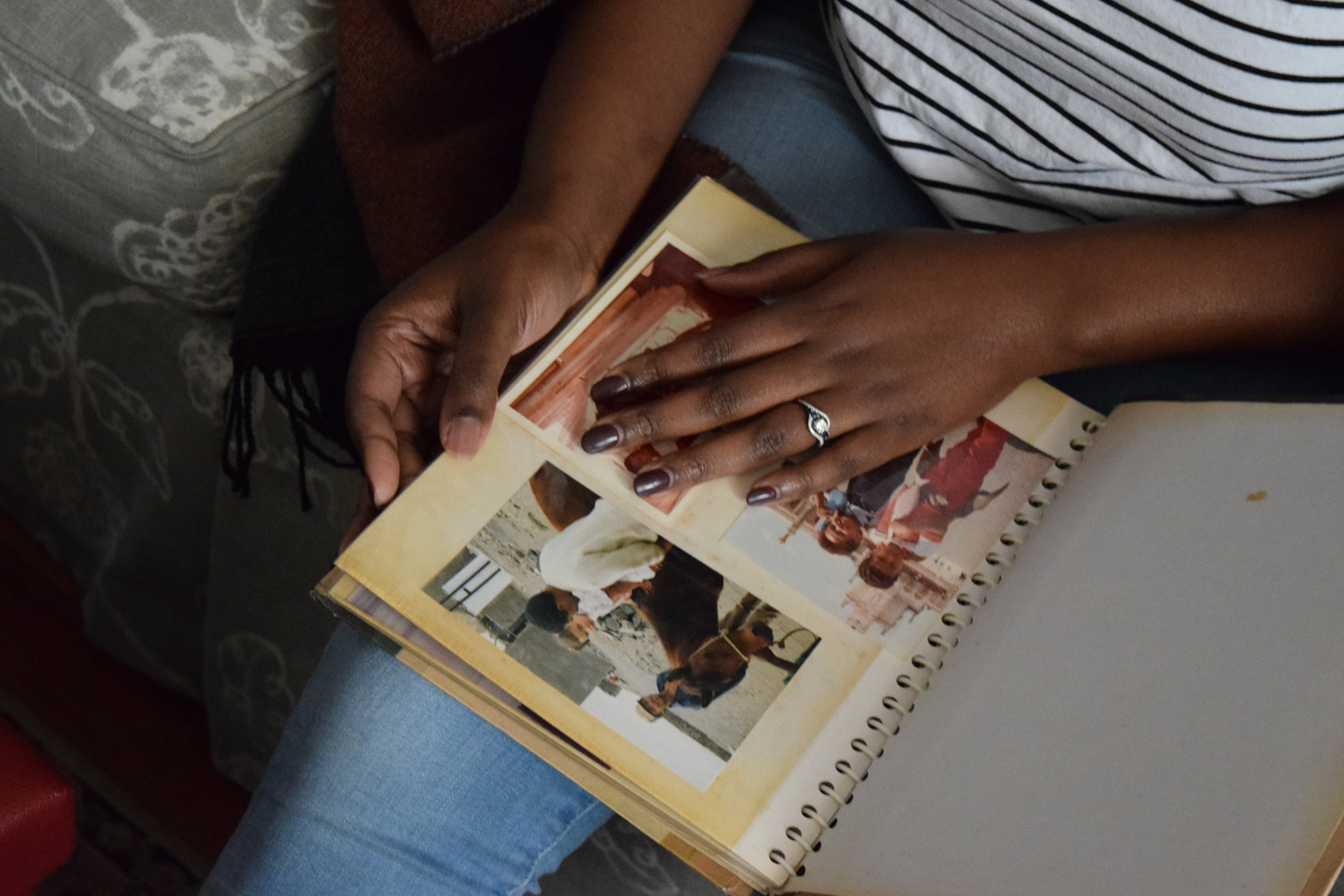 CSSJ Manager of Outreach and Community Engagement Maiyah Gamble-Rivers looks through a family photo album during an oral history session.