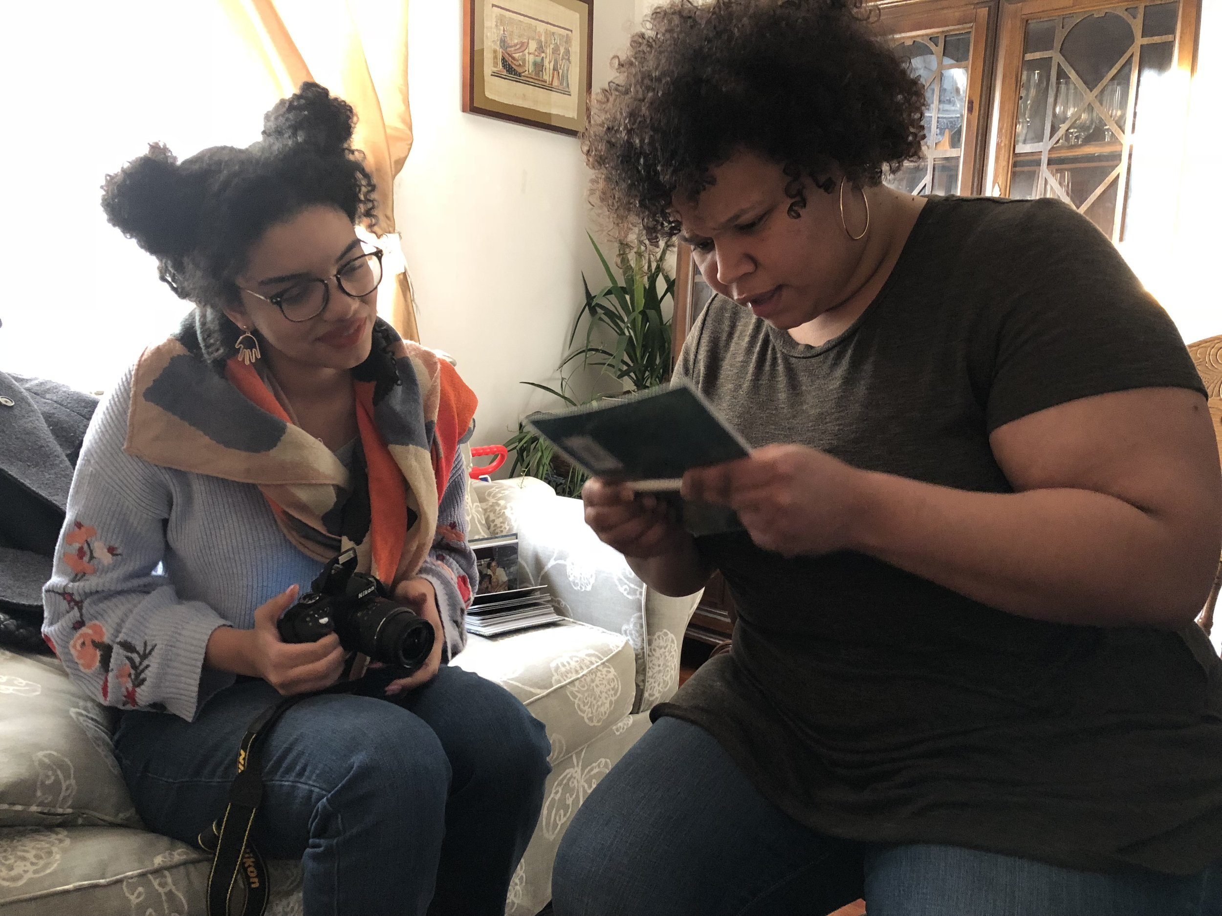 Memory Dishes  curator Johanna Obenda looks at family photograph with Margarida da Graça during an oral history session.