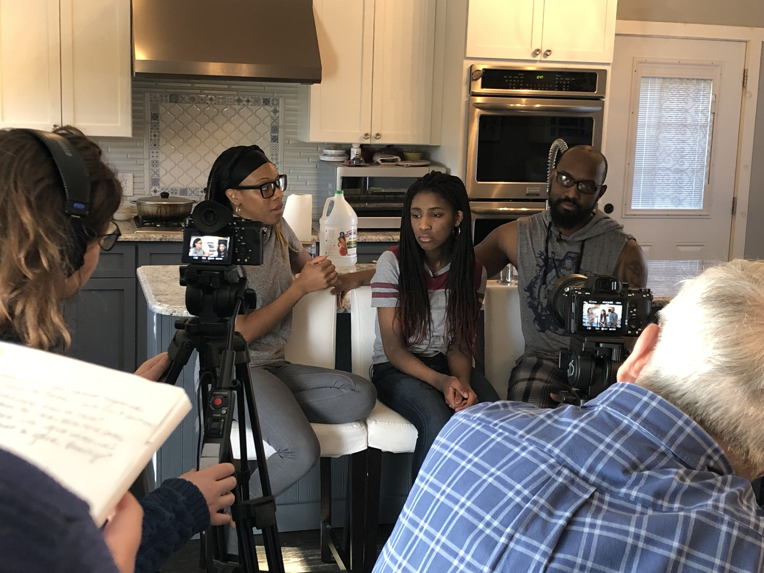 Emilia   Figliomeni (left) and Paul Rochford, Jr (right) film an interview with the Powell family during their cooking session.