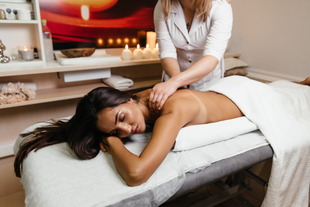 A woman lying on a bed and taking spa