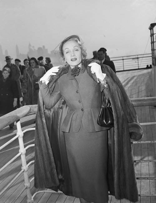 Marlene Dietrich wearing a day suit by Christian Dior onboard the Queen Elizabeth arriving in New York 21 December 1950, Getty Images