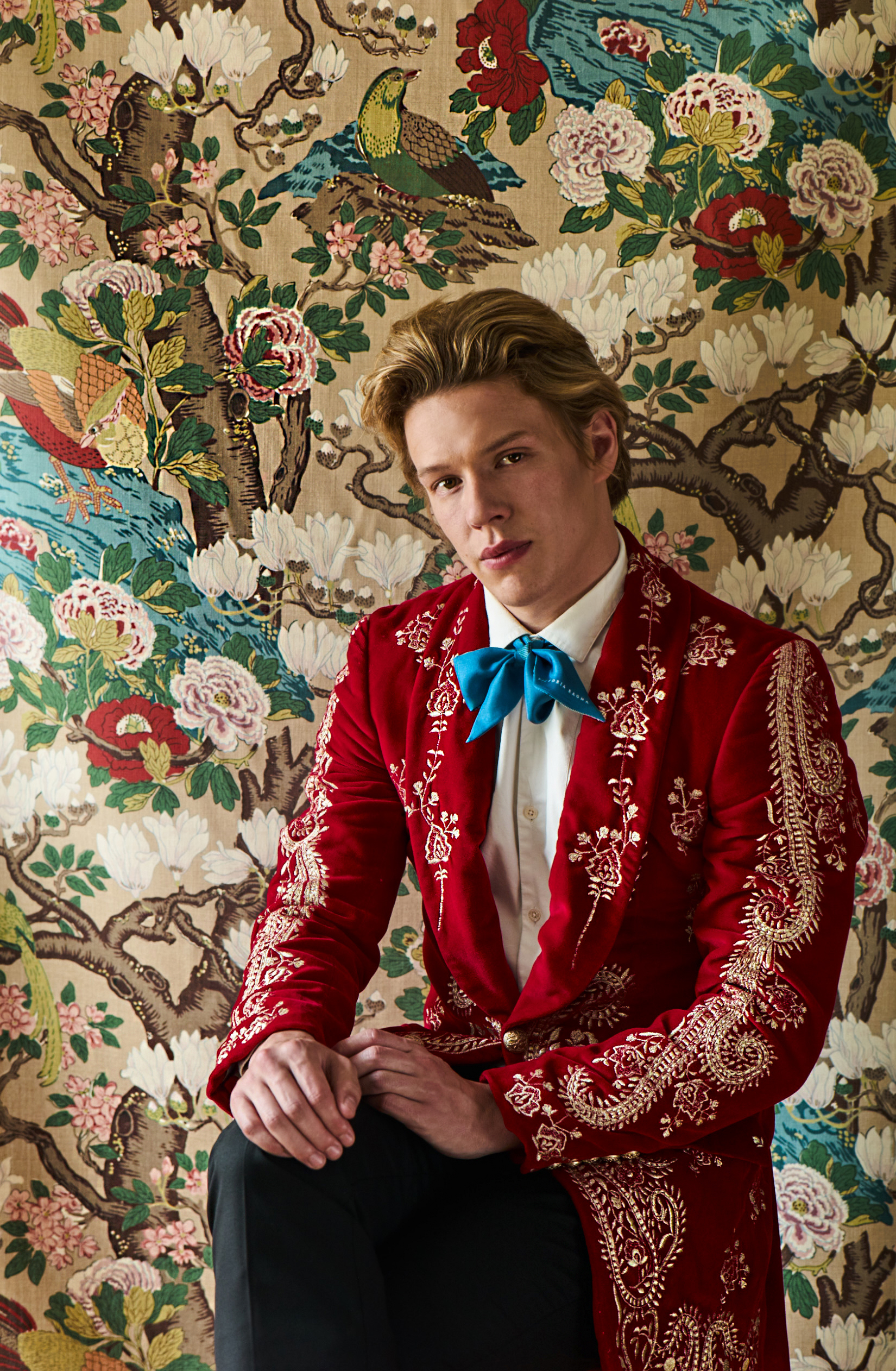 "Freddie Wise wearing red velvet blazer with gold embroidery Helen Anthony, black satin panel wool tuxedo trouser Brunello Cucinelli, printed scarf Victoria Ragna, set ""Rockbird"" fabric in multicolour GP & J Baker"