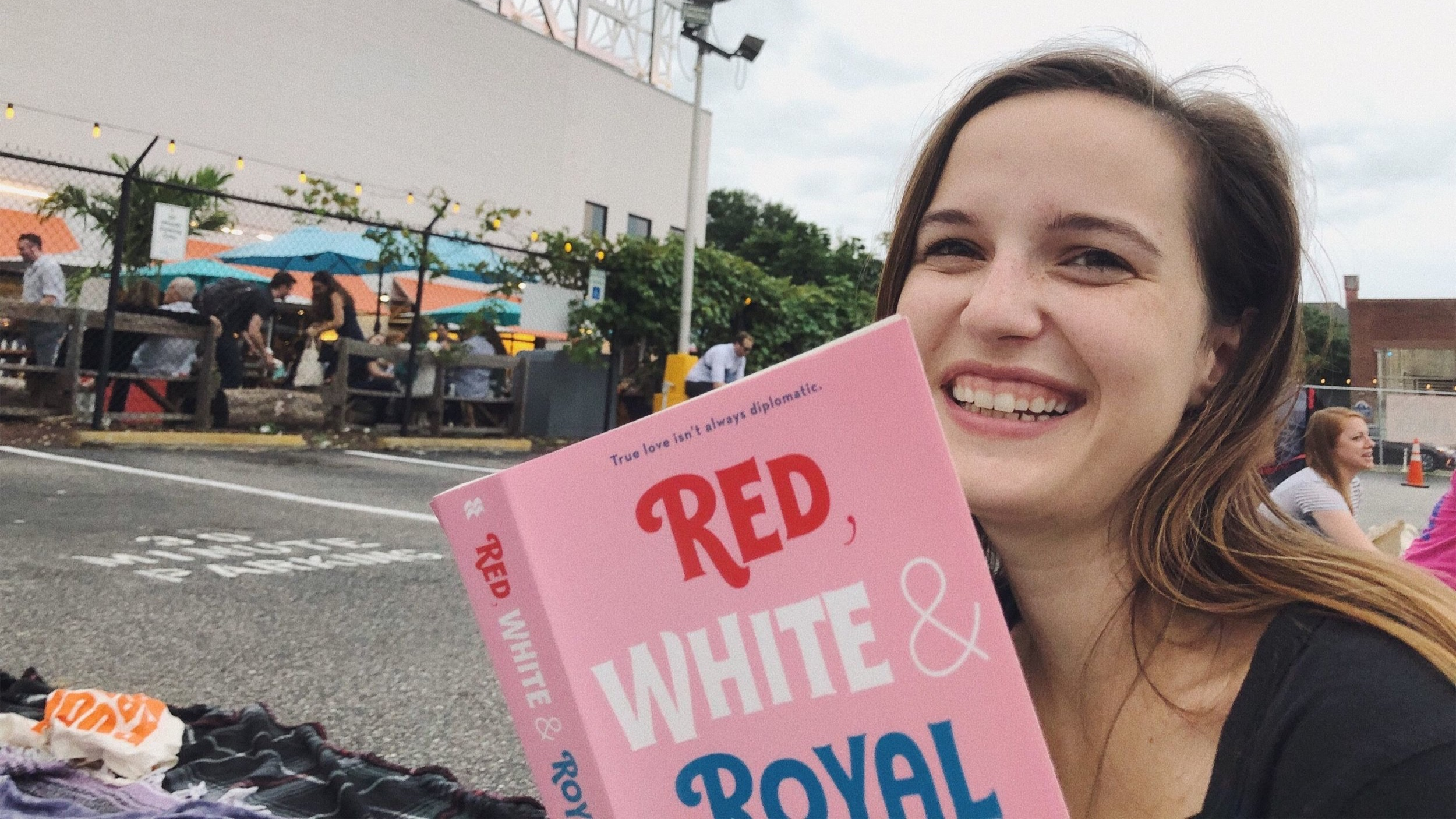"""""""Red White & Royal Blue"""" is a breakout book of the summer. It took my a few days to read, but here I am reading it before an outdoor screen of some dumb Nick Cage movie at Union Market in DC."""