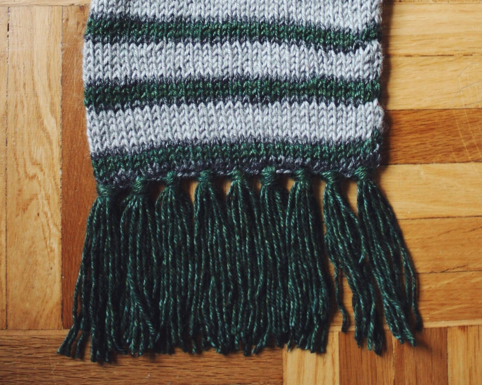 "Why buy a Hogwarts scarf when you can make your own? Pictured is a finished Slytherin ""Cursed Scarf."" Pattern here for free on emmmysue.com"