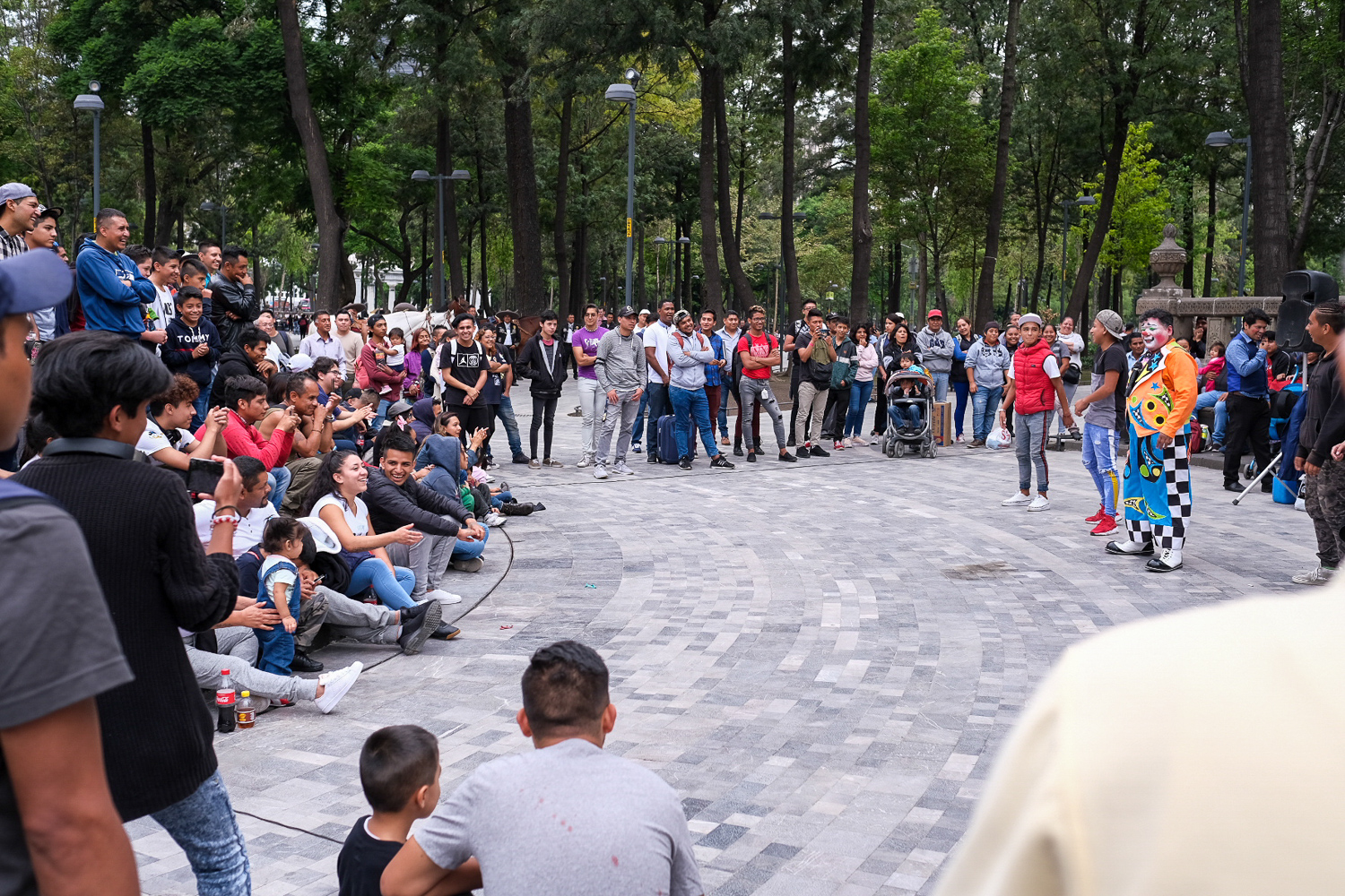 """Activating public spaces can be simple. I am jealous of the amount of public spaces found in Mexico City and Puebla. Plazas, placitas, plazuelas, shaded walkways, public benches are abundant in Mexico. They are central to public life and, on any given evening, it is easy to find crowds of people enjoying the parks in their own way. Above is one example. I'm not sure why, but clowns are really popular in Mexico. They captivate crowds of people sitting in ad hoc stadium seating, made of sidewalks, fountain ledges and monuments. Within a few meters of this clown show in  Alameda Central , there were ice cream vendors, rappers battling each other, and young couples enjoying some pizza on a park bench. The plaza is simply built, with very little in terms of what we would consider """"park fixtures."""" No basketball courts, no fields, no jungle gym. No signs telling you what you can't do. The  Alameda Central  is a blank canvas on which the people of the community paint a beautiful collage made up of their favorite activities."""
