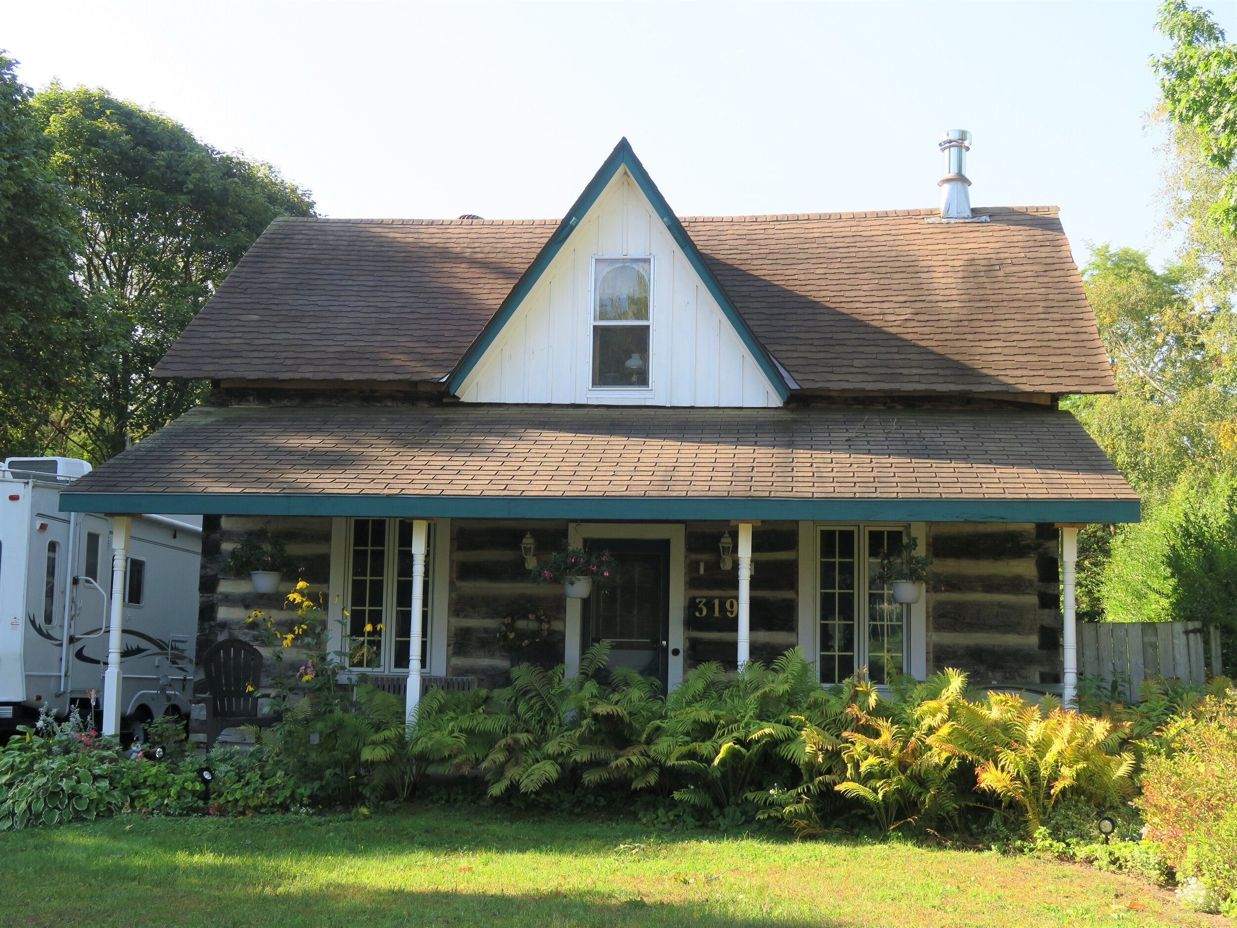 319 Saugeen St, built c.1867 by John MacLean (1803-1882) is a log house with a round-headed window in the centre gable.
