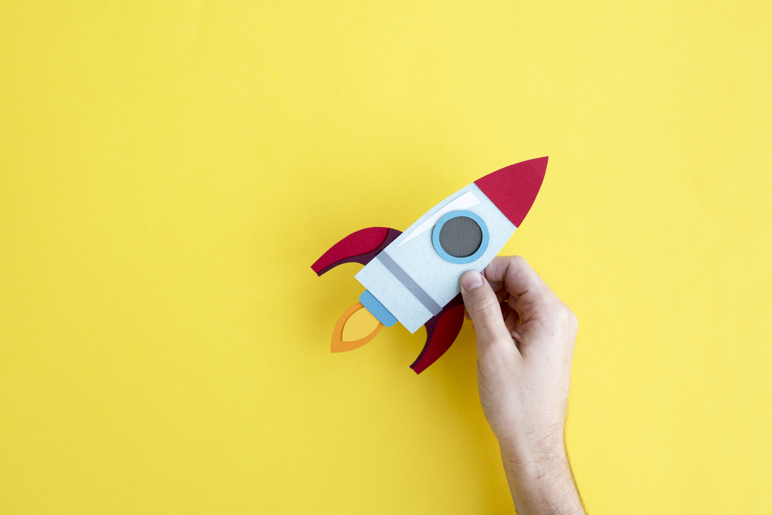 hand-holding-rocket-spaceship-on-yellow-PFKQACP.jpg