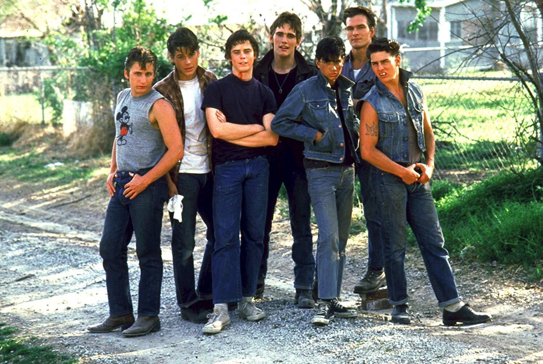 Da esq. para a dir.: Two-Bit (Emilio Estevez), Sodapop (Rob Lowe), Ponyboy (C. Thomas Howell), Dallas (Matt Dillon), Johnny (Ralph Macchio), Darrel (Patrick Swayze) e Steve (Tom Cruise). Tá bom para você?