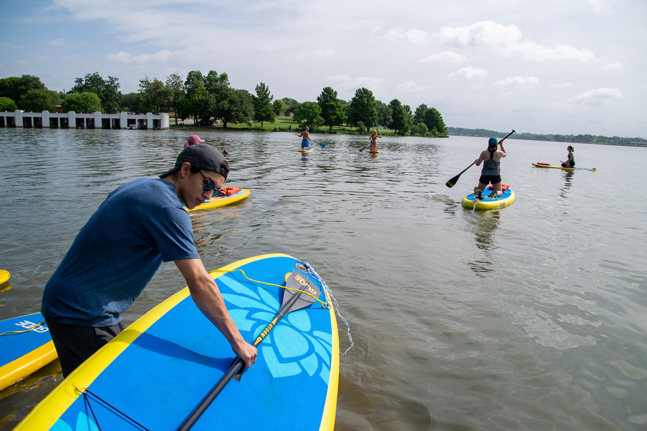 Yogis begin launching into White Rock Lake to practice yoga on paddle boards.