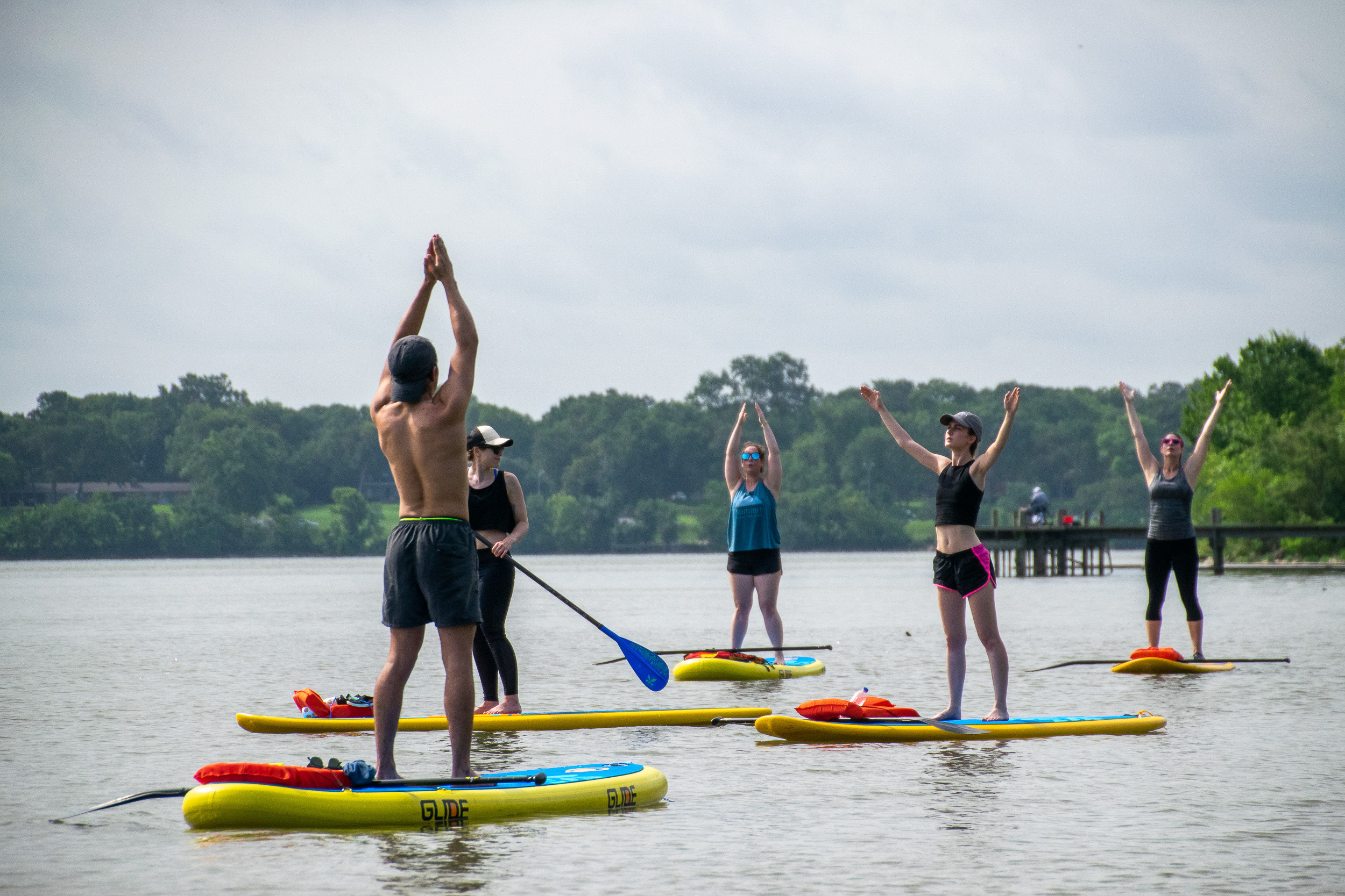 Yogis stretch on paddle boards at White Rock Lake in Dallas.