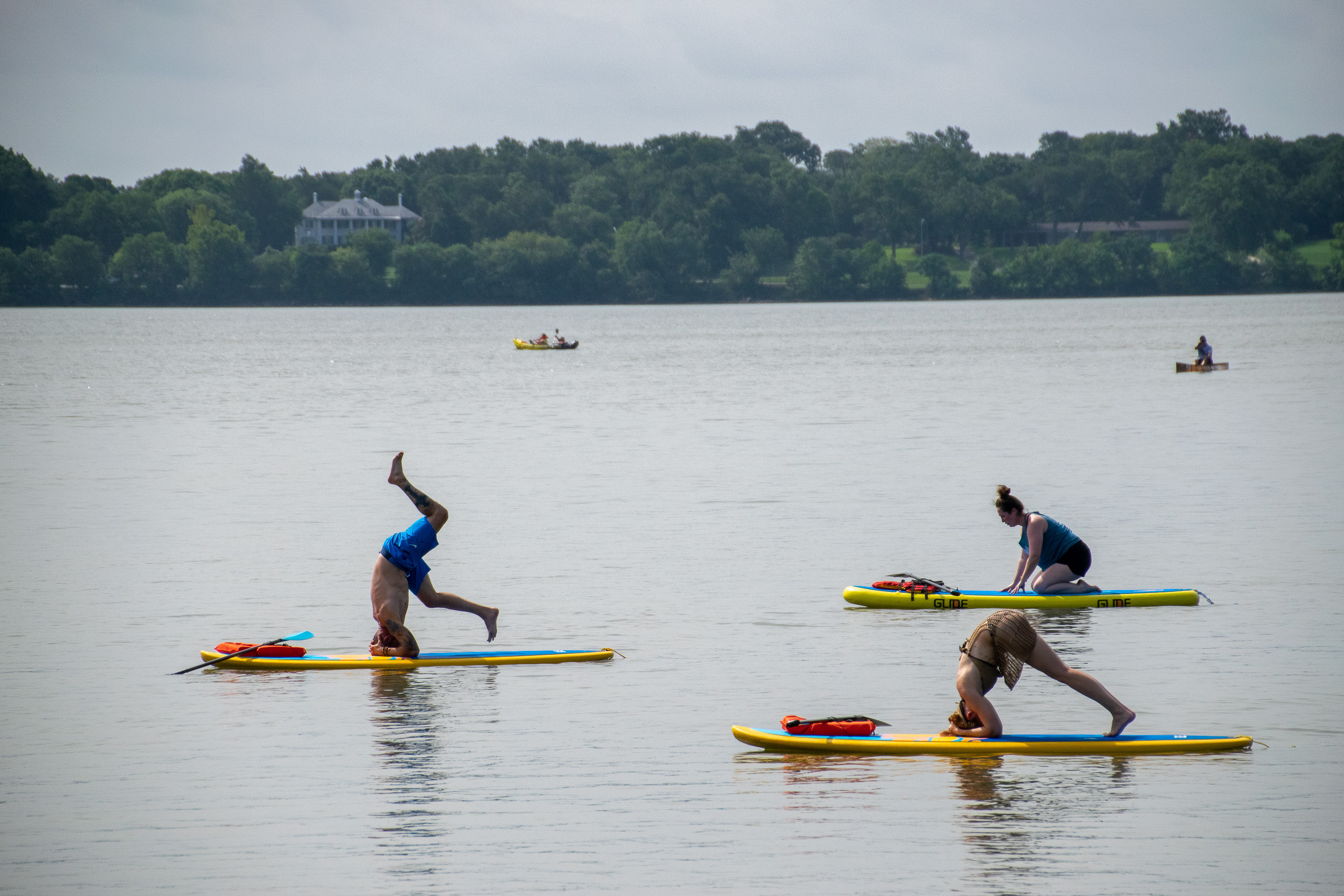 Yogis attempt kicking into headstands while balancing on stand up paddle boards on White Rock Lake in Dallas.