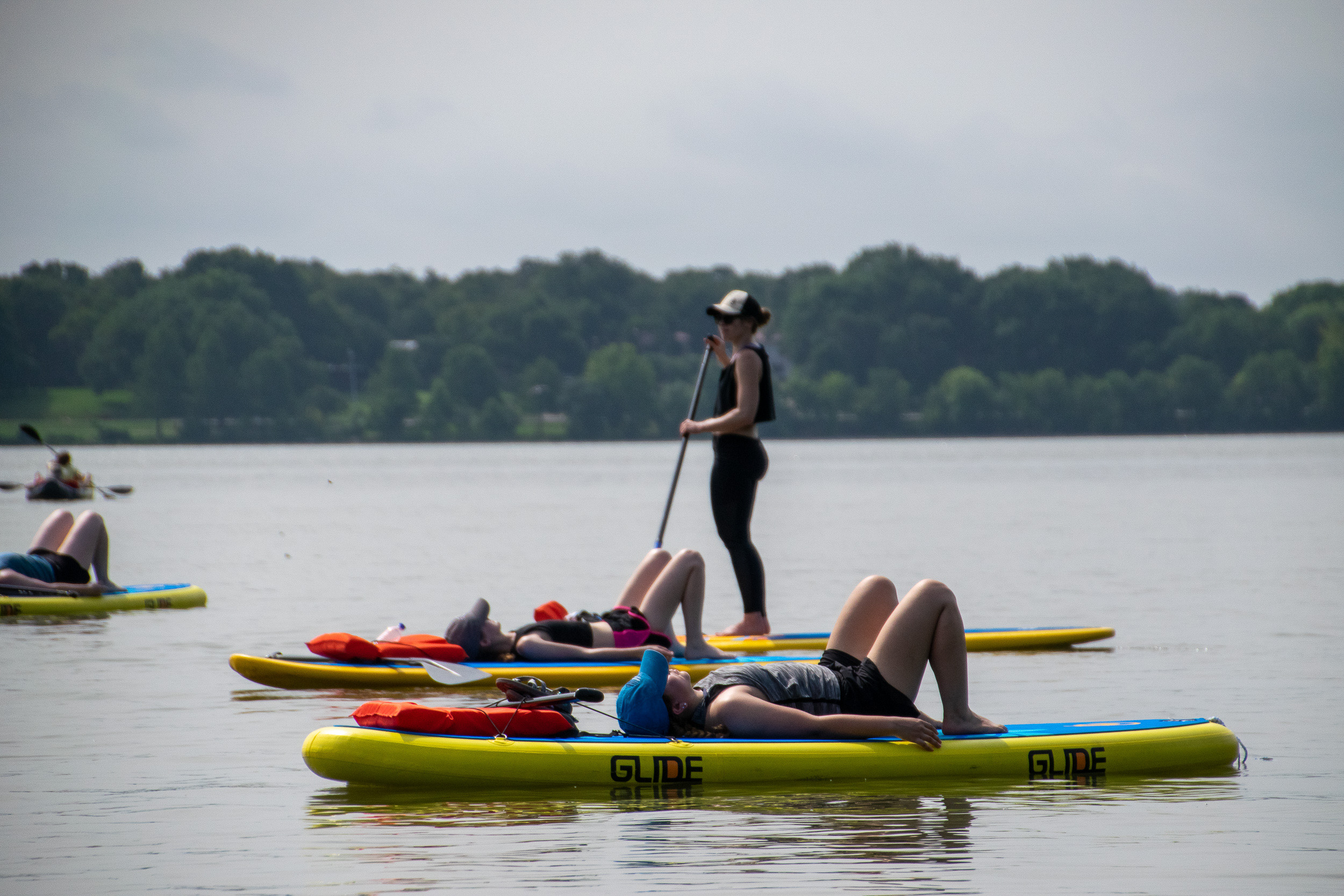 Instructor Tory Christopherson-Sommerfeldt of Just Be Well Yoga surveys her group of paddle boarding yogis in the water at White Rock Lake in Dallas.
