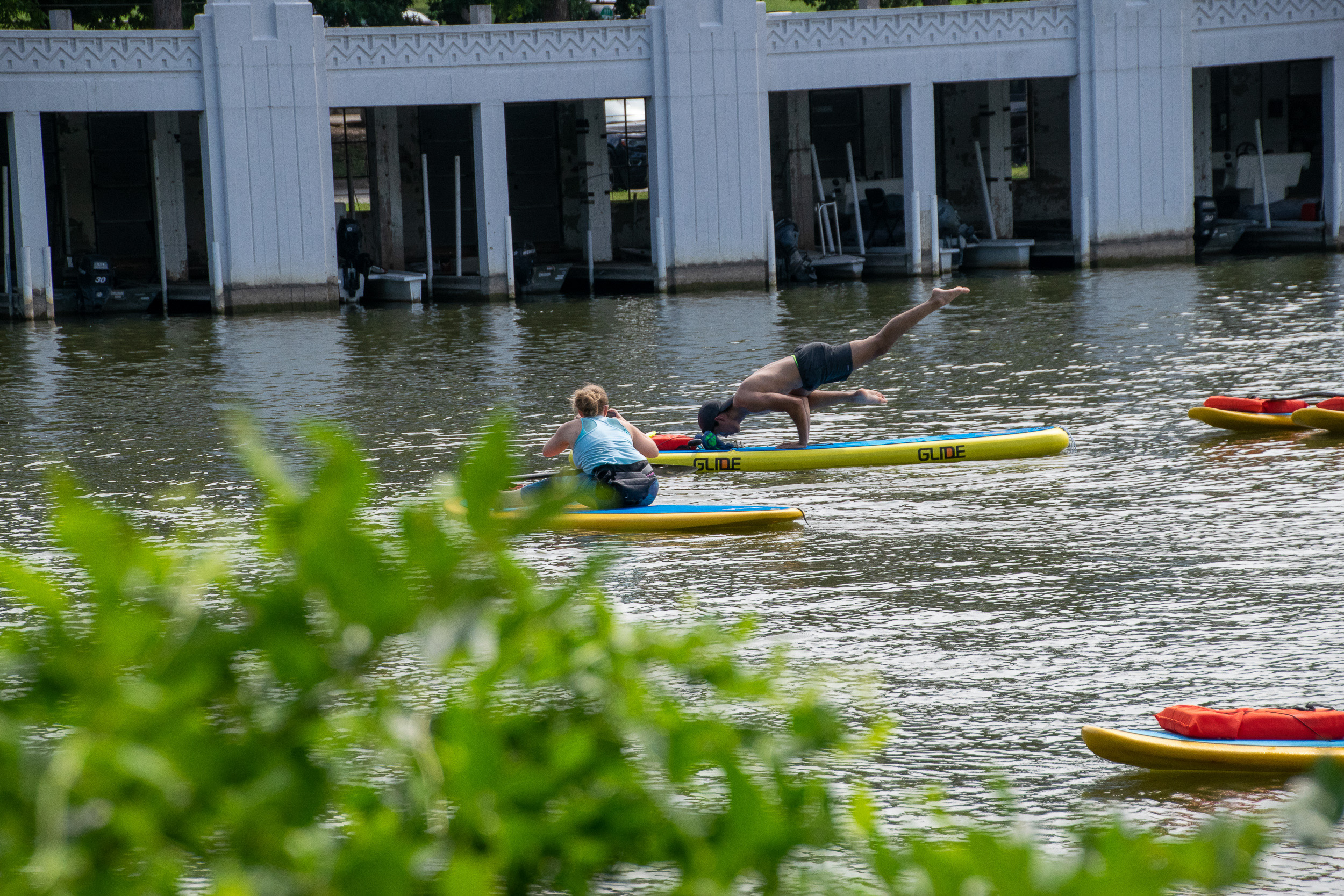 One yogi strikes a flying pigeon pose on his paddleboard as Amanda Quintanilla, Just Be Well Yoga founder, photographs from her board.