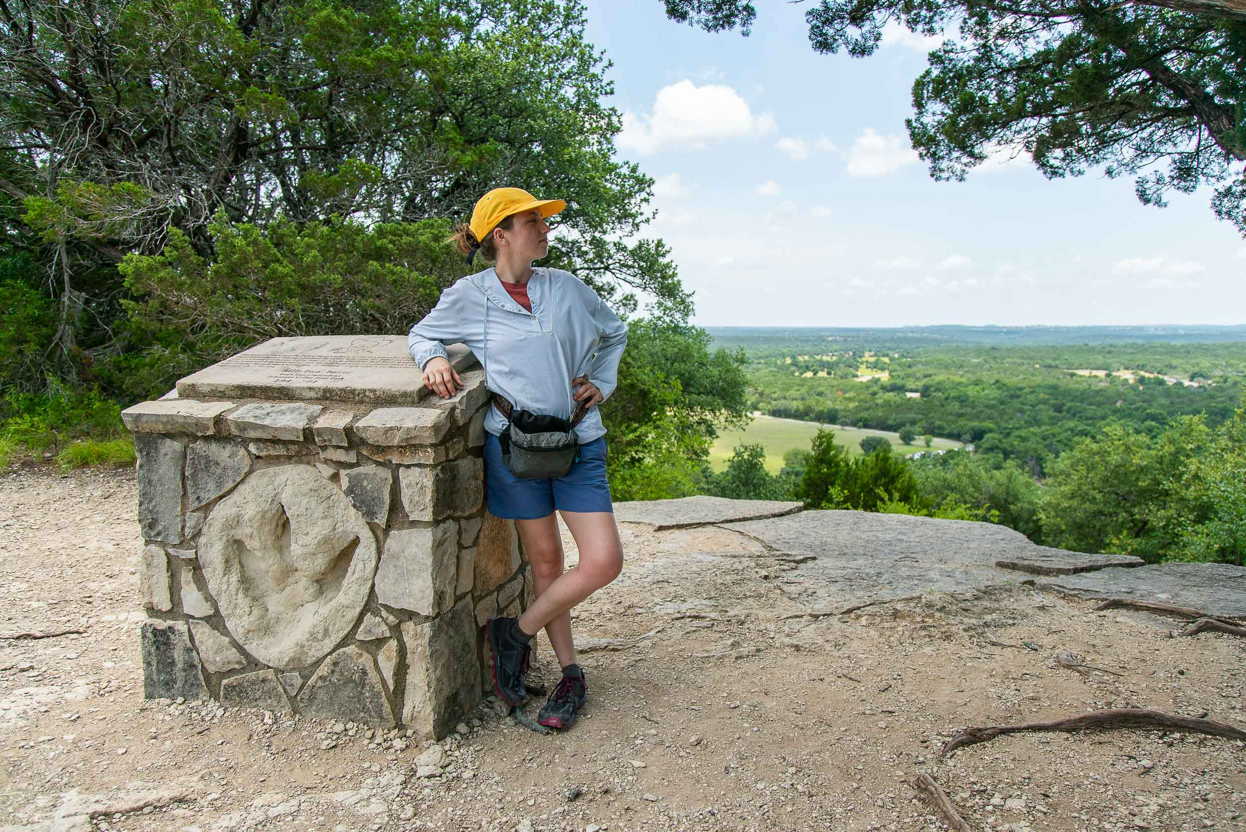 Sarah Mowery standing with the monument that marks the top of the Overlook Trail and honors one of Dinosaur Valley State Park's stewards by  Cameron Mosier .