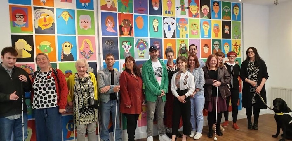 Some of the project's participants and facilitators in front of the portrait wall