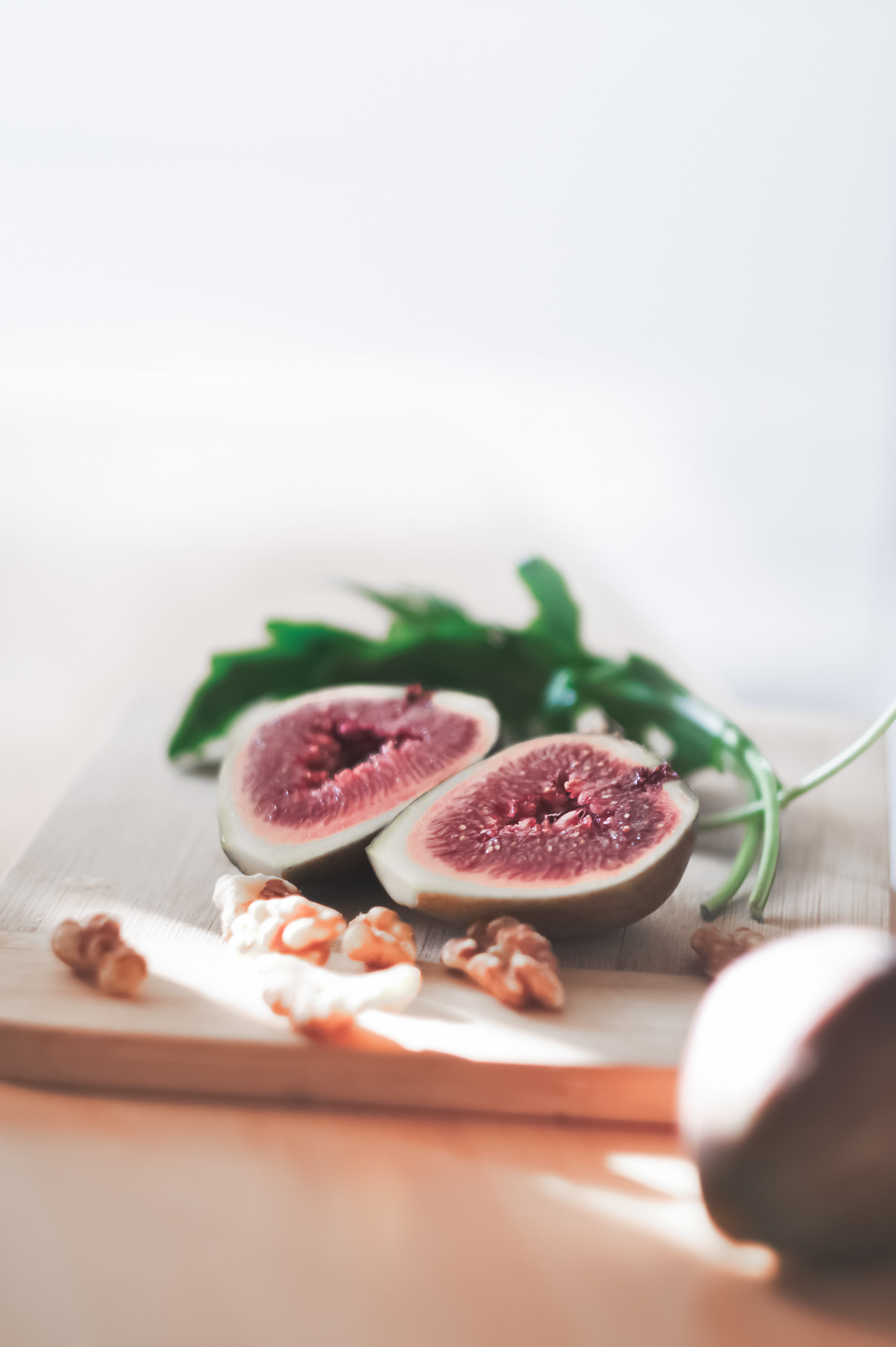 chopping board with figs, walnuts and rocket