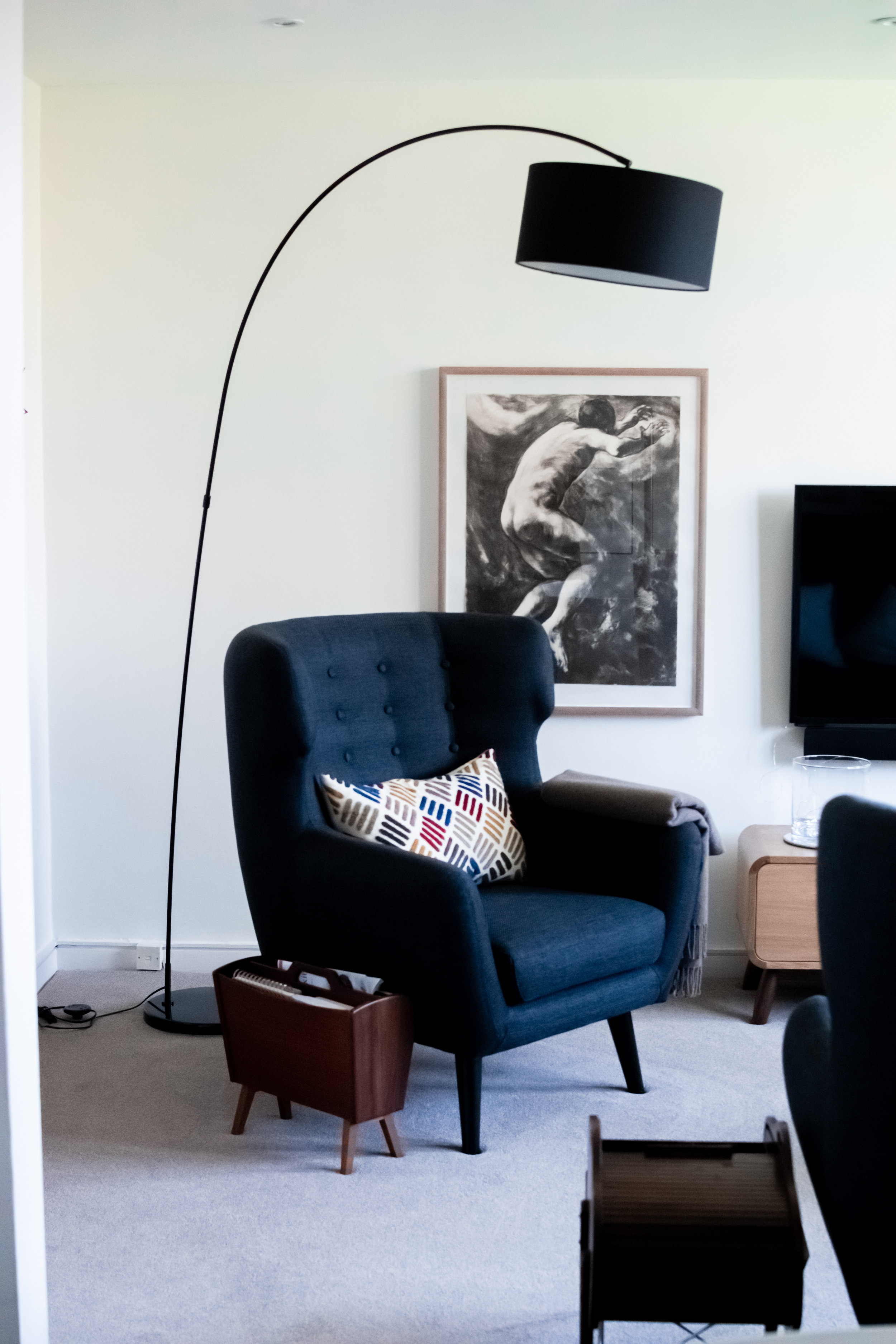 Navy blue armchair with lamp, art and mid-century accessories
