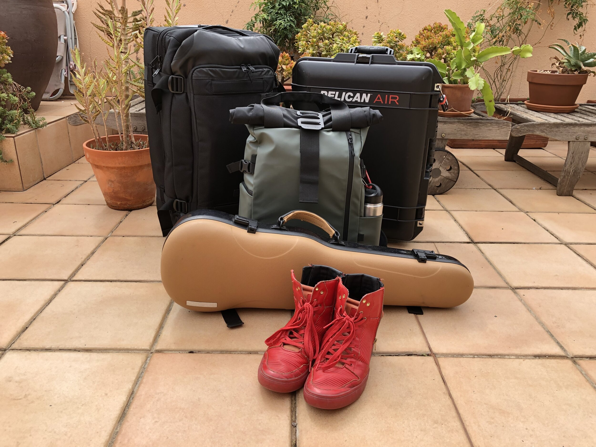 One bag for clothes, one case for A/V gear, one backpack for day trips & quick access, one case for a 5-string fiddle, and one pair of red shoes to rule them all.