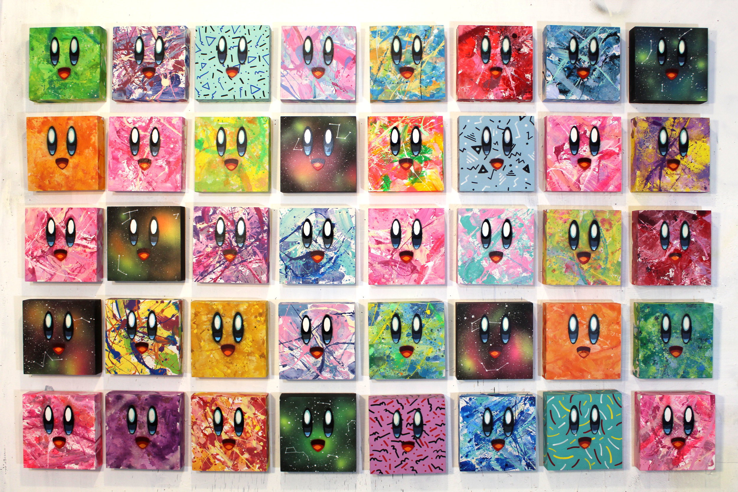 Abstract Kirby Blocks. I wanted to do paintings of my favorite Nintendo character, but I wanted to incorporate what he's also known for: A cute face and many colors. Taking that idea, I have a blast throwing paint around, making 90's patterns or a space background. In the end, each Kirby is one of a kind.