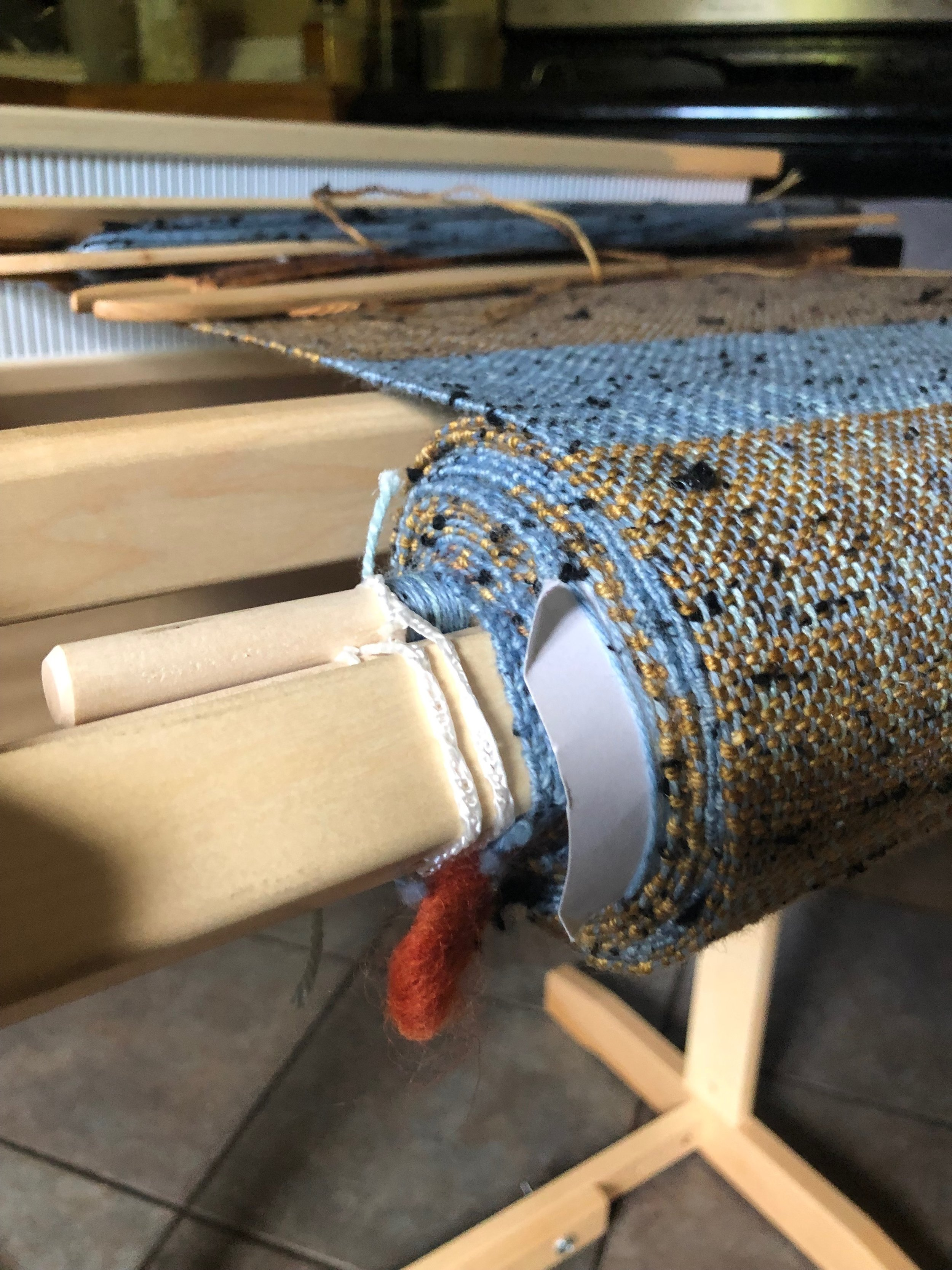 Roll of handwoven fabric in blue and gold on a loom.