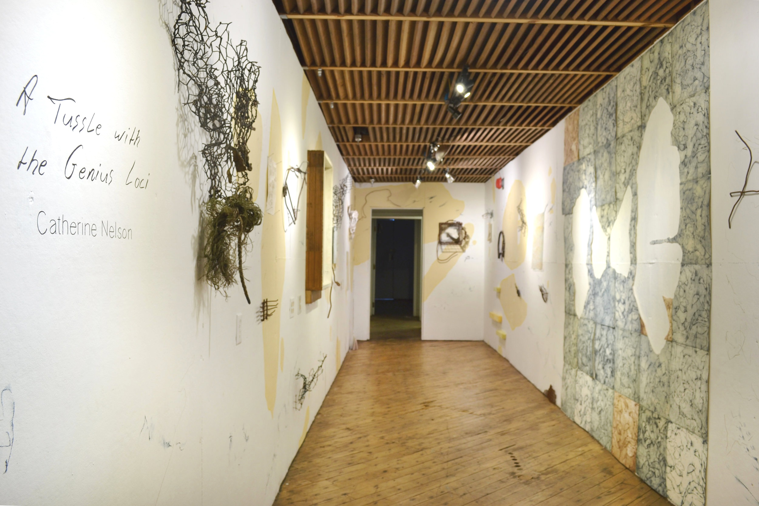 Nelson's installation, composed with tea-dyed collagraph prints, steel collage sculptures, found objects, drawings on glass, papier mache, surface prints from the bayou, and direct wall drawing