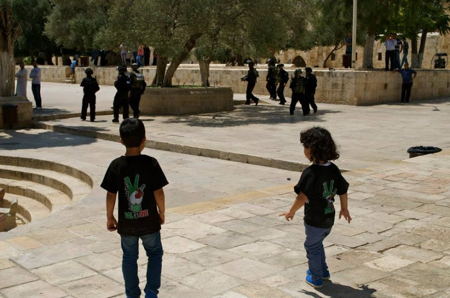 Two young Palestinian boys follow Israeli Defense Force soldiers at Al-Aqsa compound during an IDF raid in June 2014. | Rasha Abousalem
