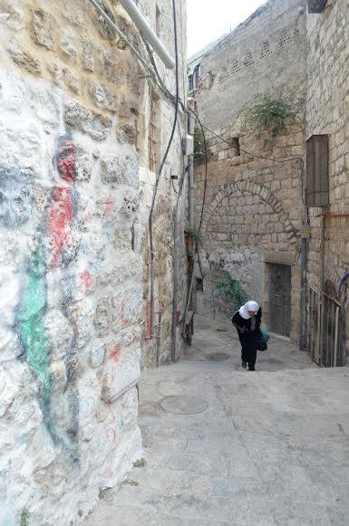 A Palestinian woman walks through Old Jerusalem City, Palestine. | Photo by: Rasha Abousalem