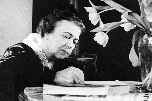 An older Alexandra Kollontai writing her memoirs