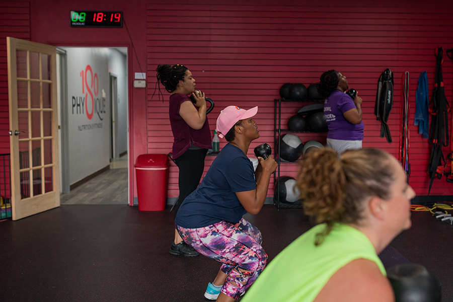 woman doing squats with dumbbell at 180Physique's 180FitSquad