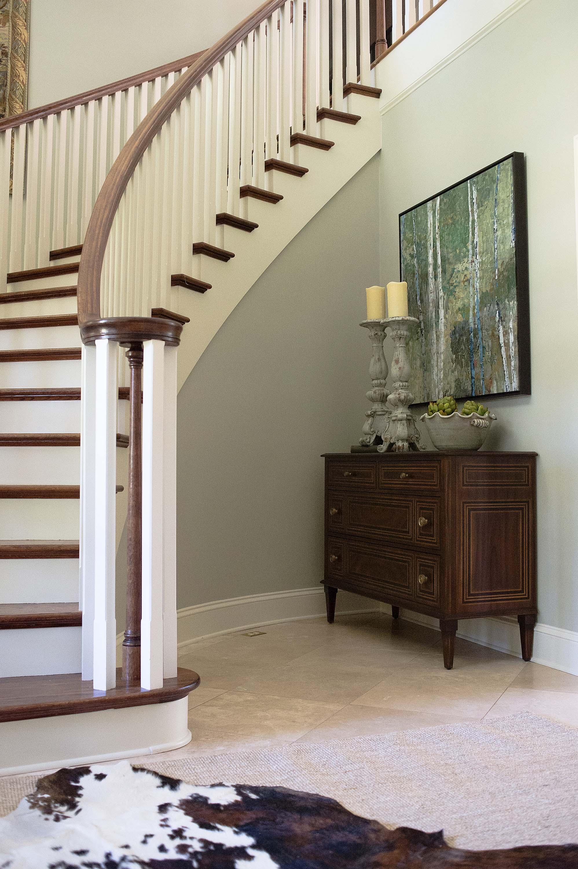 House interior with wooden staircase, vintage style drawer and frame on the wall