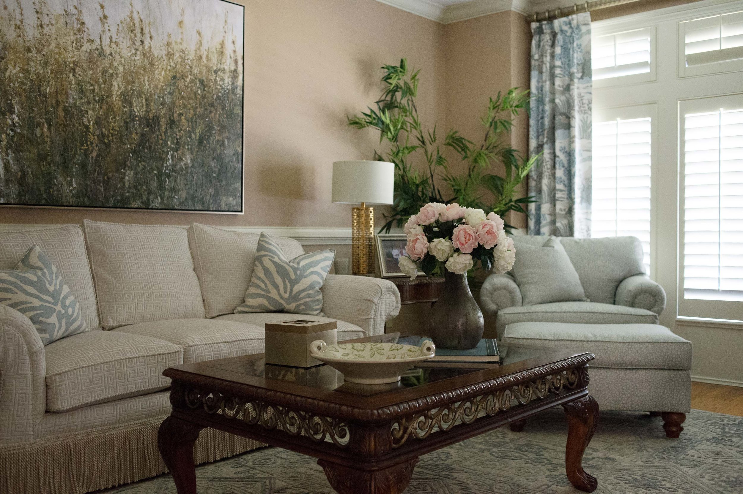 Living room with sofa, wooden center table, large frame on the wall and indoor plant
