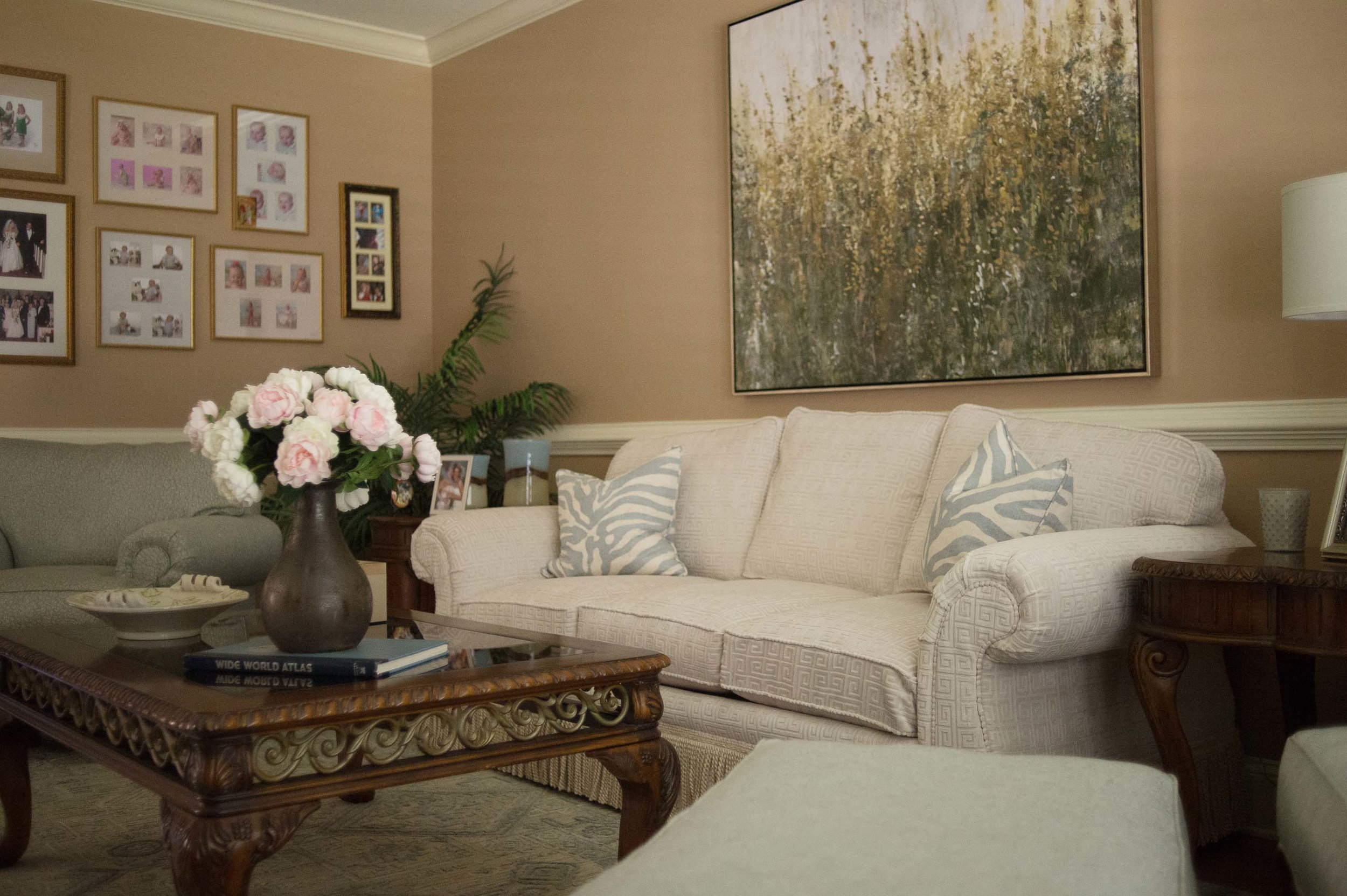 Living room with sofa, wooden center table and family pictures frames on the wall