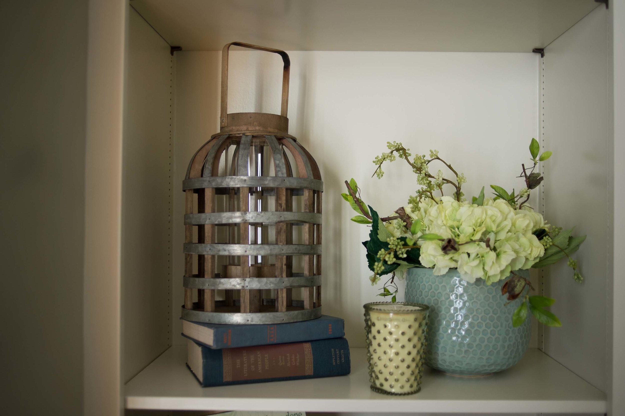 Shelf with books, lantern, candle and flowers on a vase