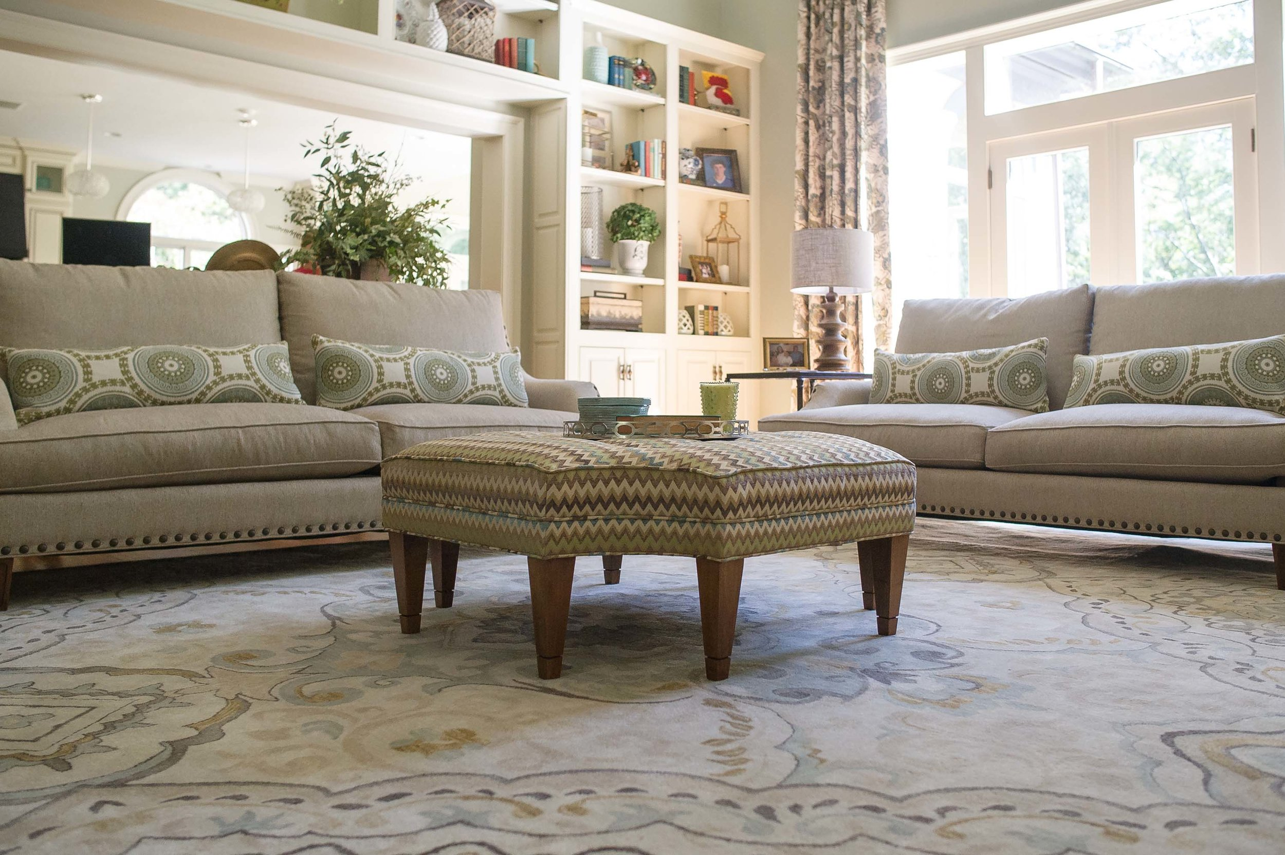 Living room with large carpet, ottoman, and sofa