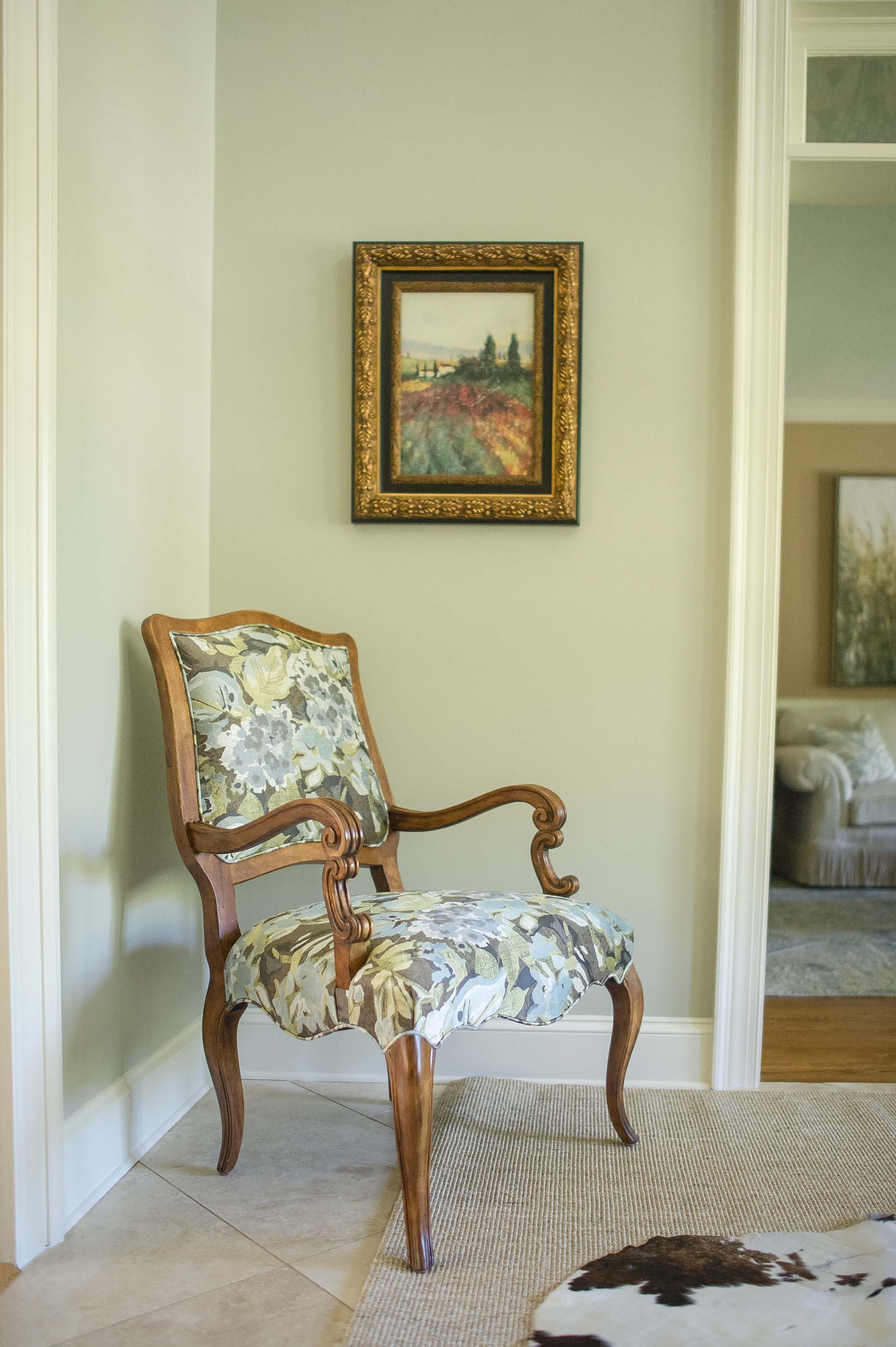 House interior with wooden armchair and a frame on the wall