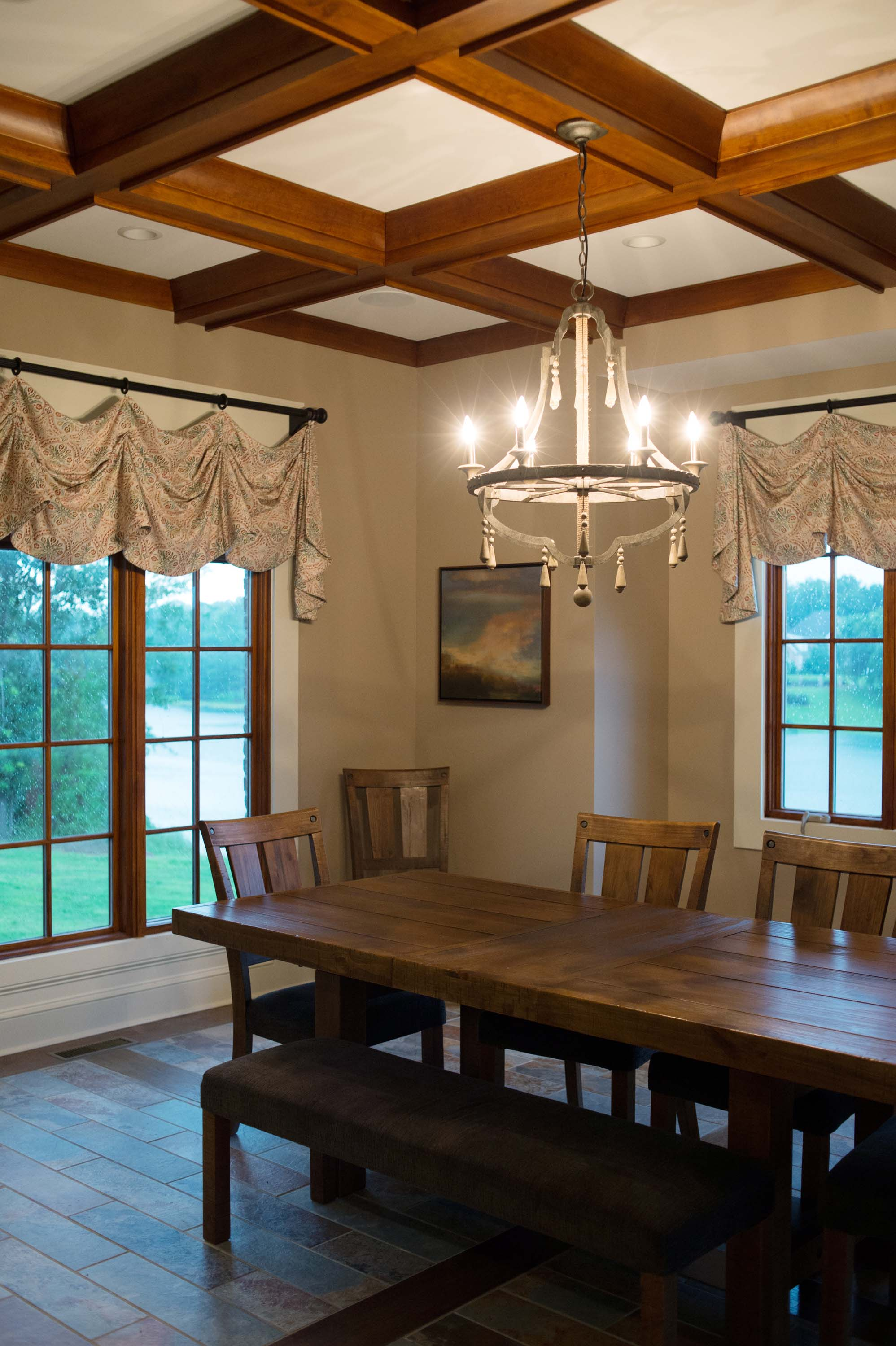 Dining room with wooden table and chairs, large windows and chandelier