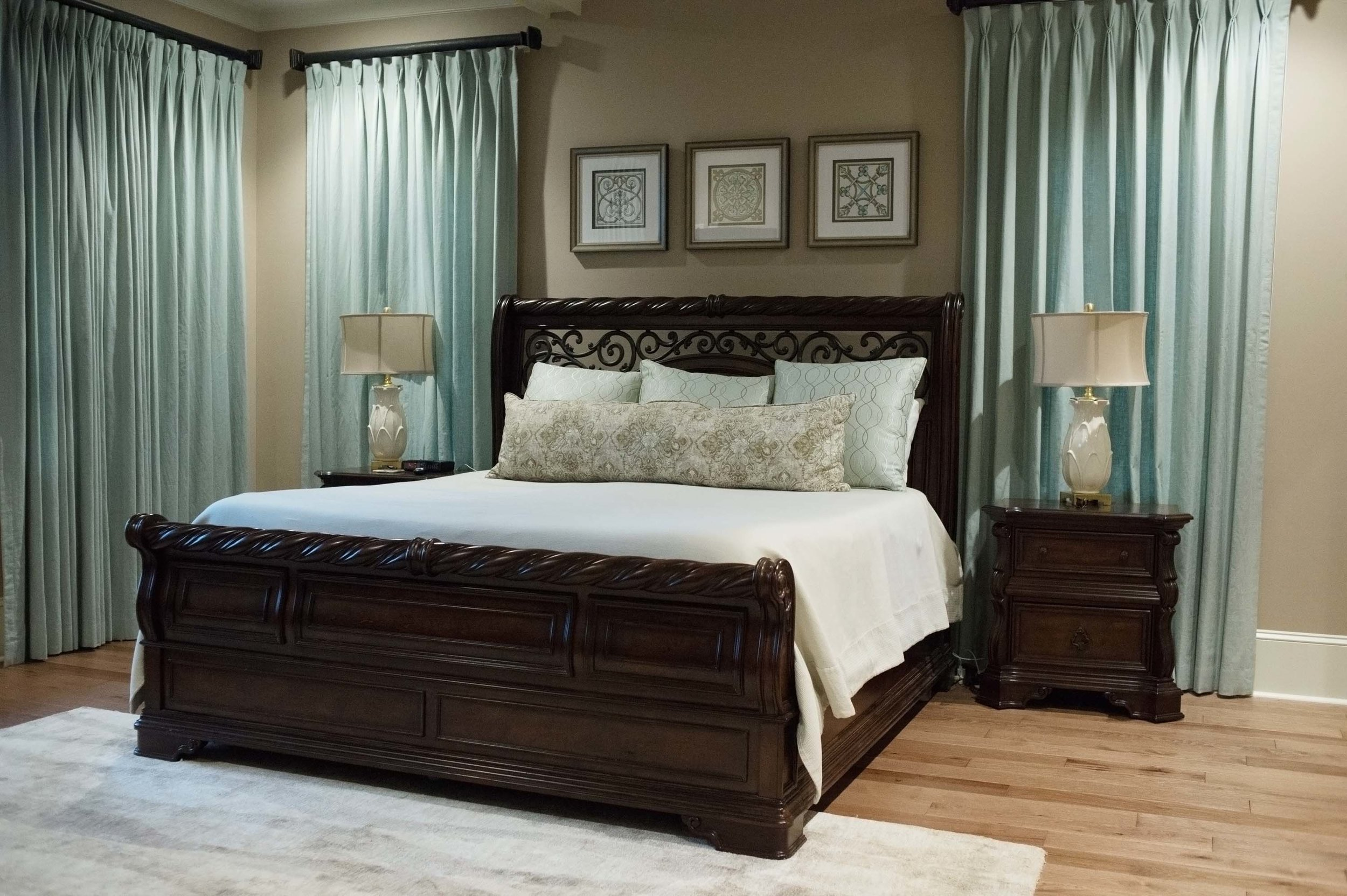 Bedroom with wooden bed, wooden bedside tables, table lamps and a hardwood floor