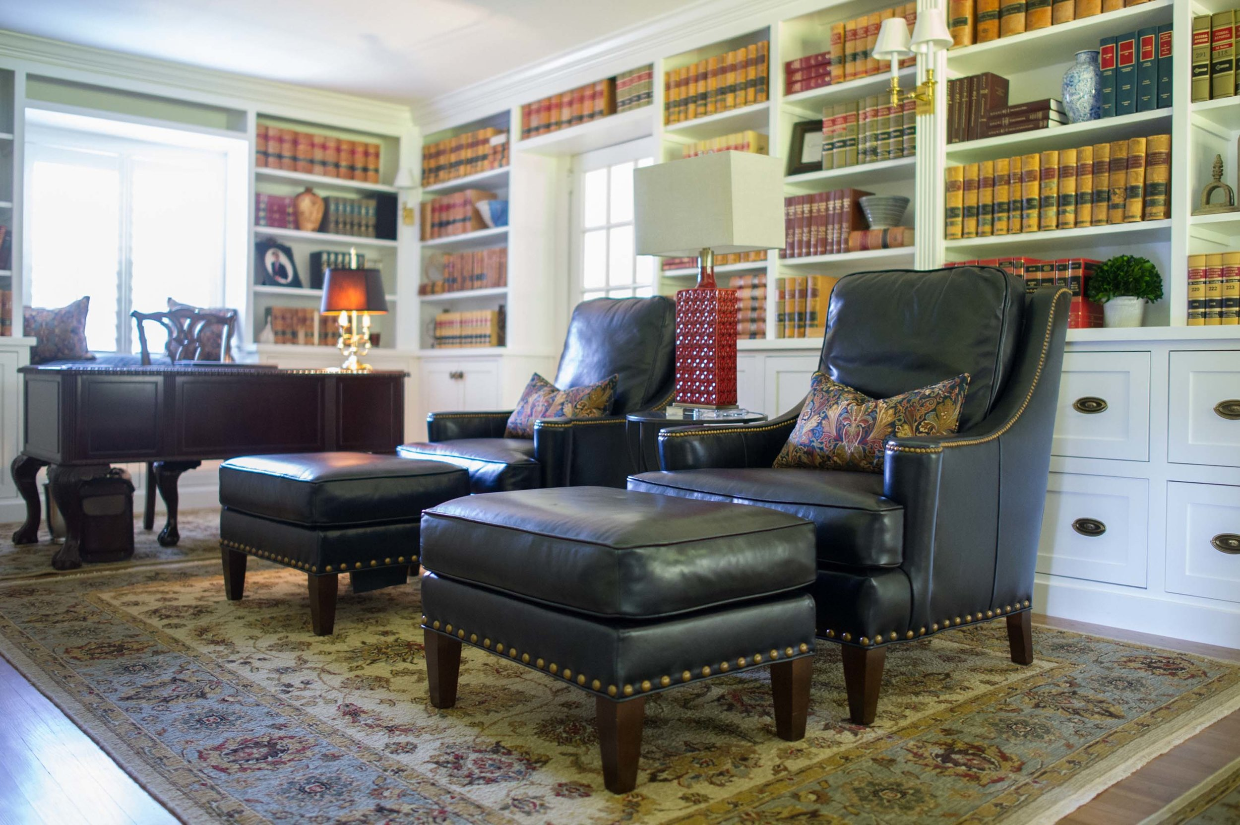 Home library with arm chair, ottoman, large carpet and wooden white shelvesrpet and wooden white shelves