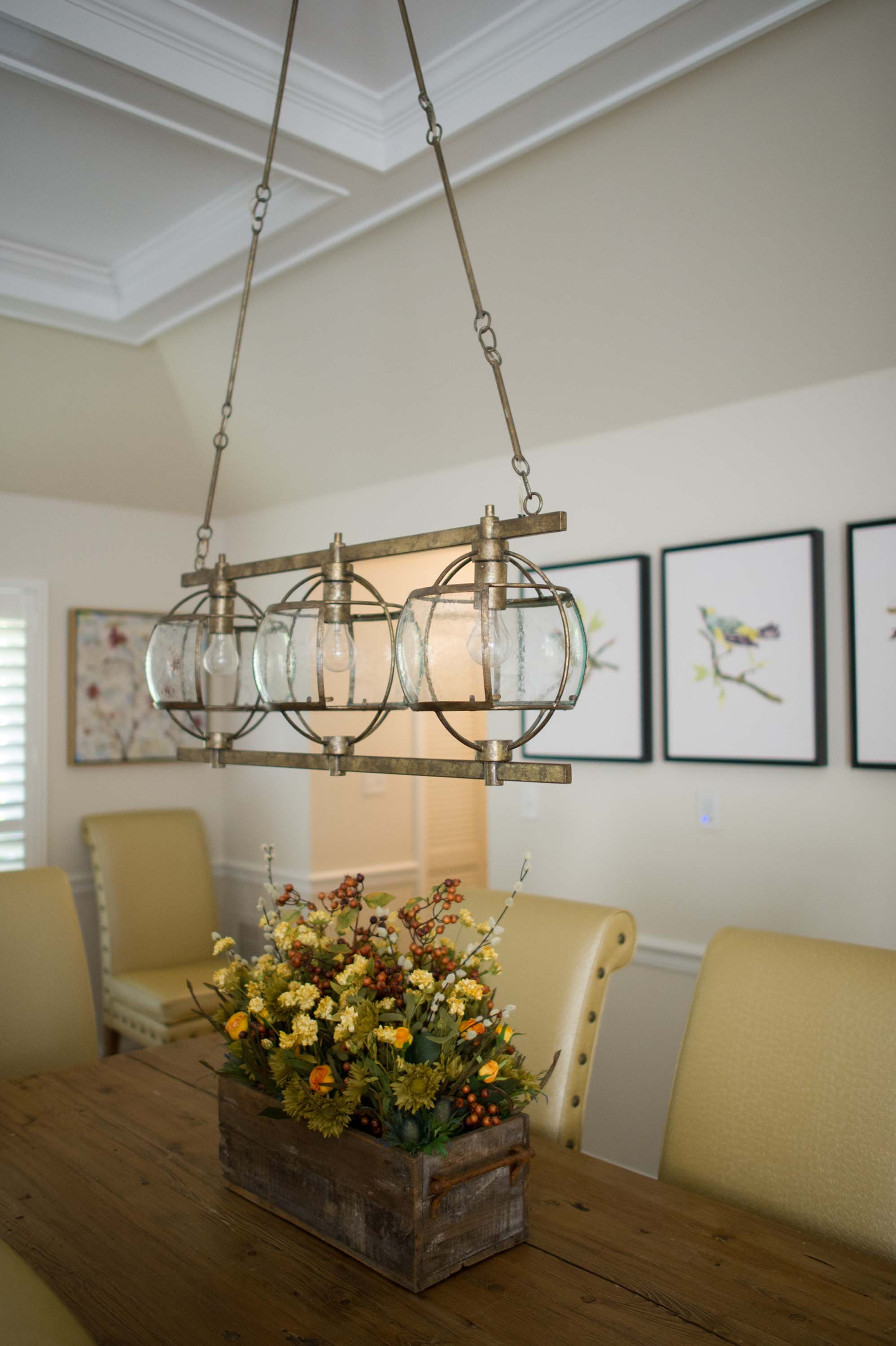 Dining room with wooden table, flowers on top and modern style hang ceiling lamp