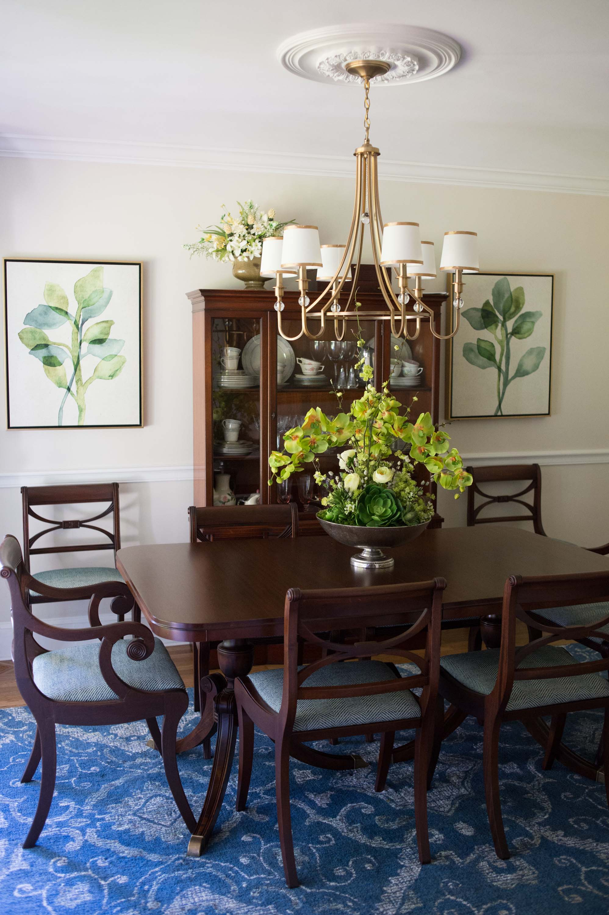 Dining room with wooden table, chairs, cabinet and chandelier
