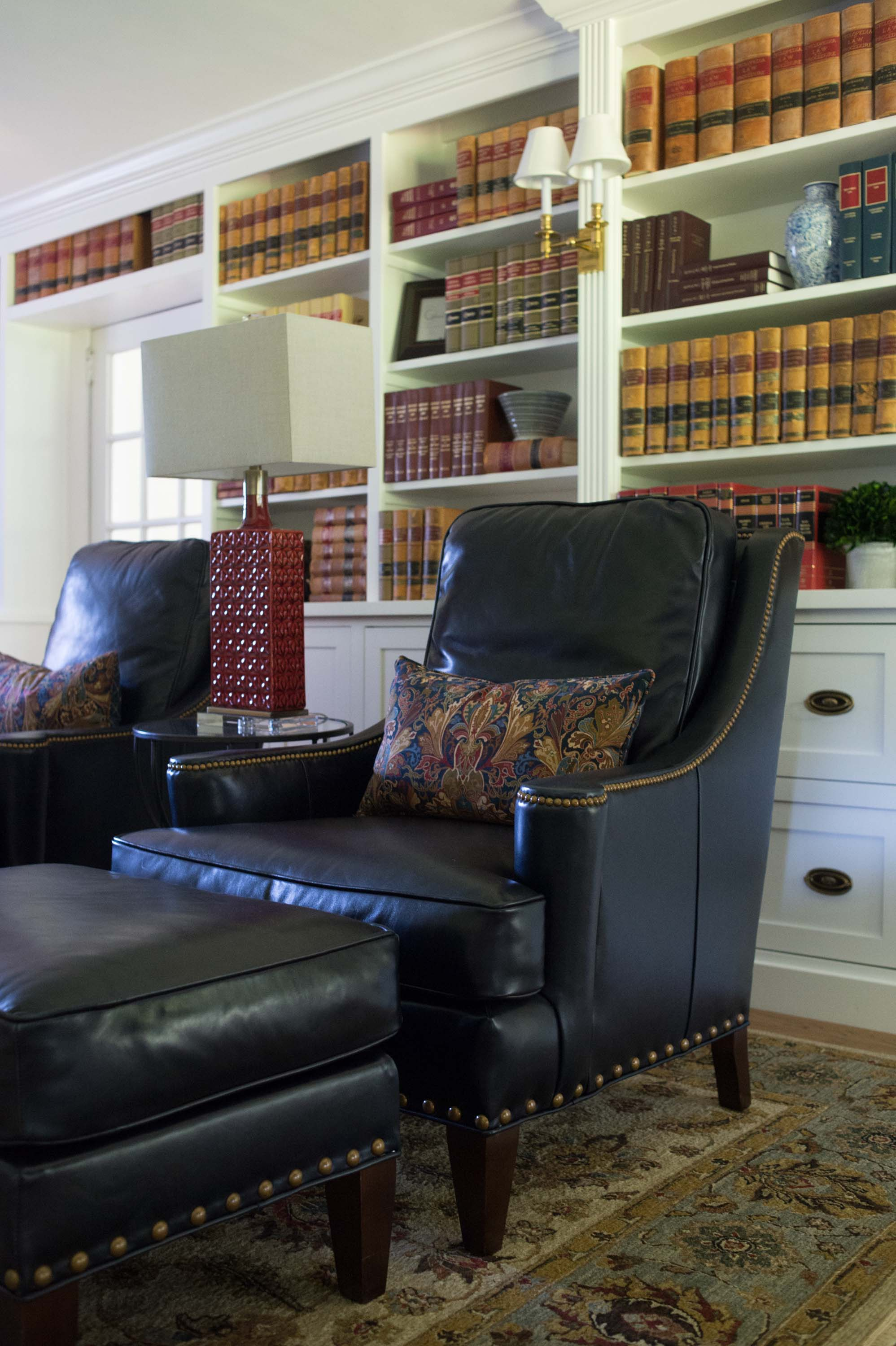 House library with arm chair, ottoman and white book storage