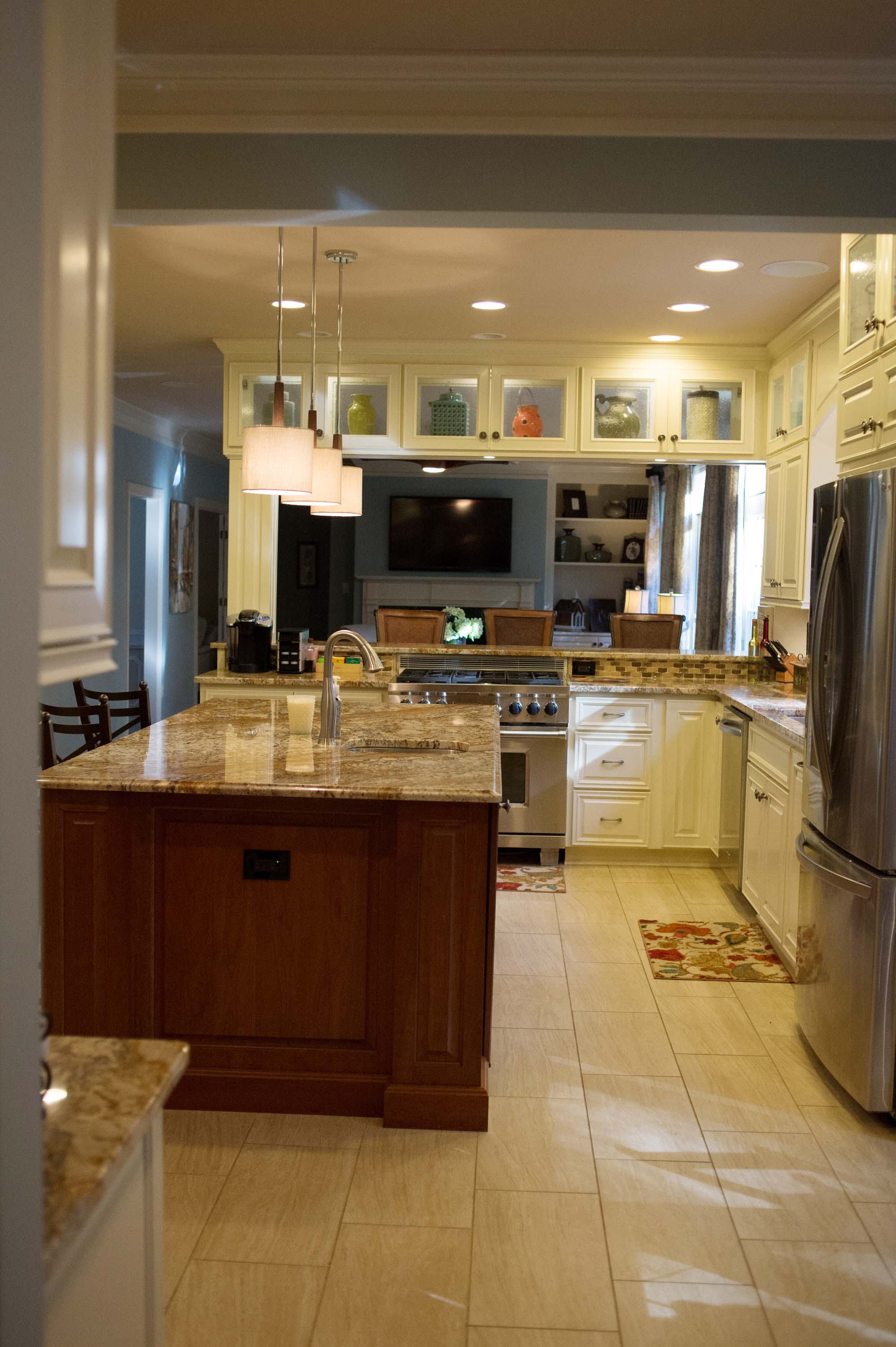 Kitchen with fridge, cabinets, wooden center island and ceramic countertops