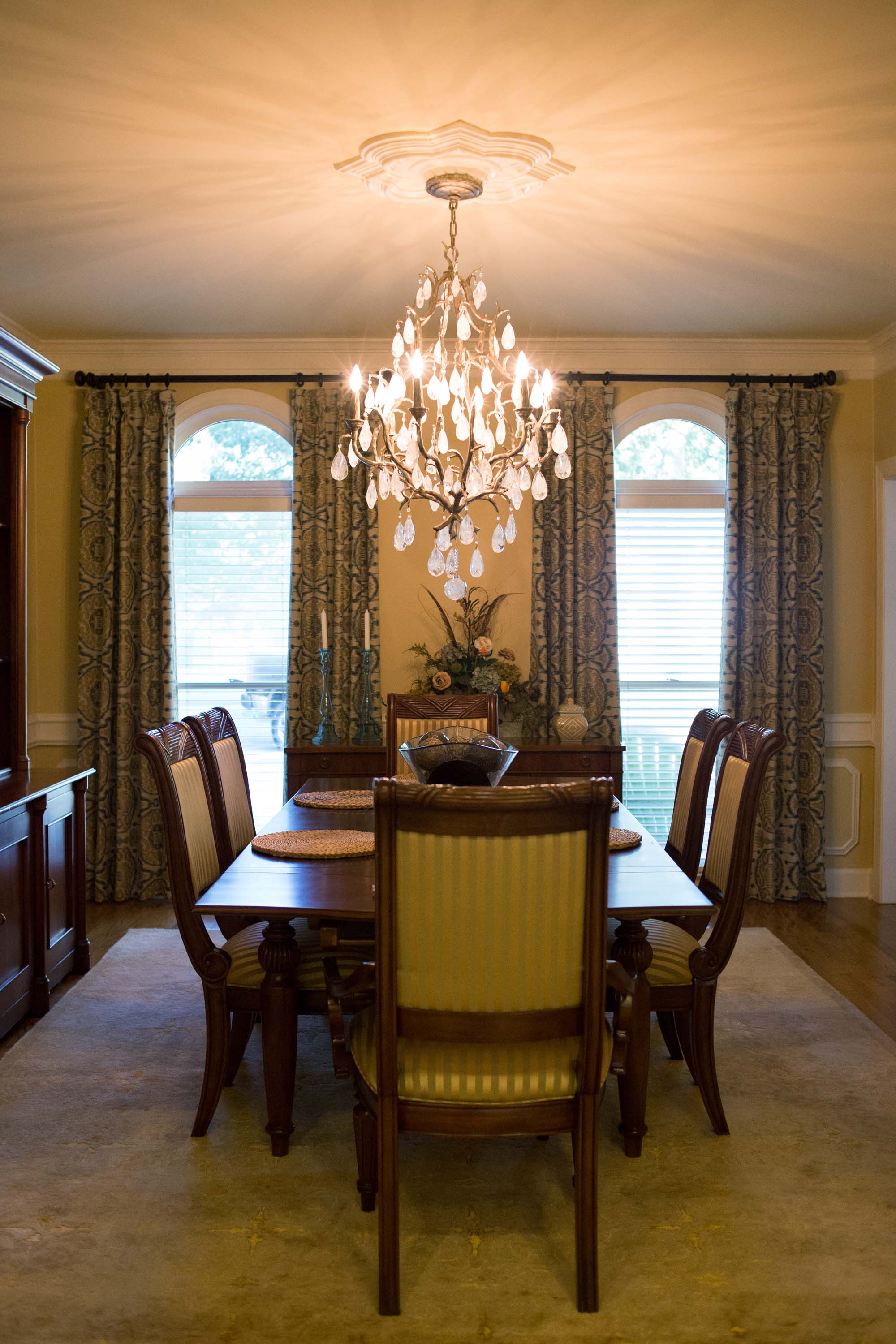 Dining room with wooden table, chairs and chandelier