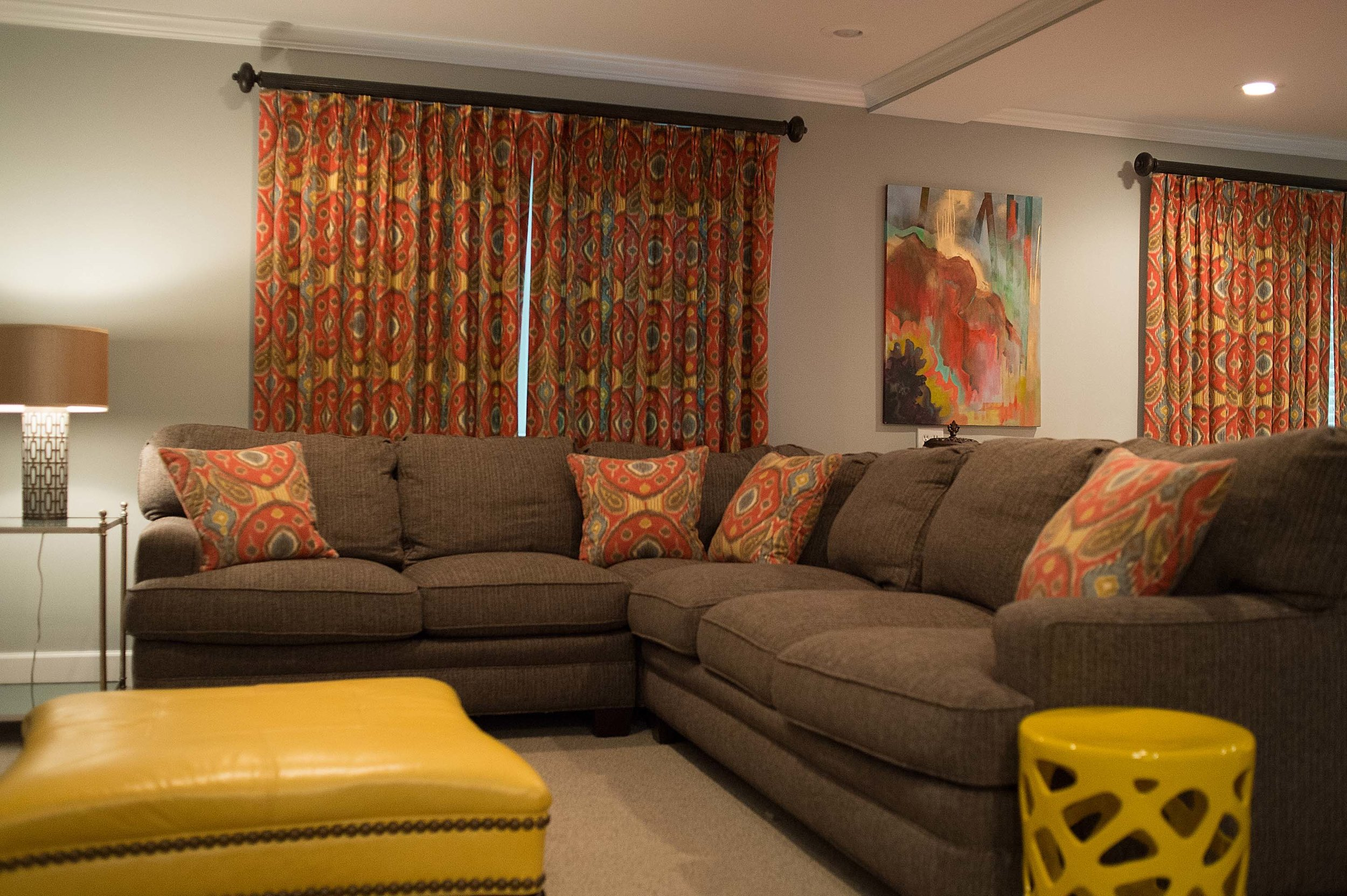 Living room with pillows and curtains of the same fabric, large sofa and artwork on the wall