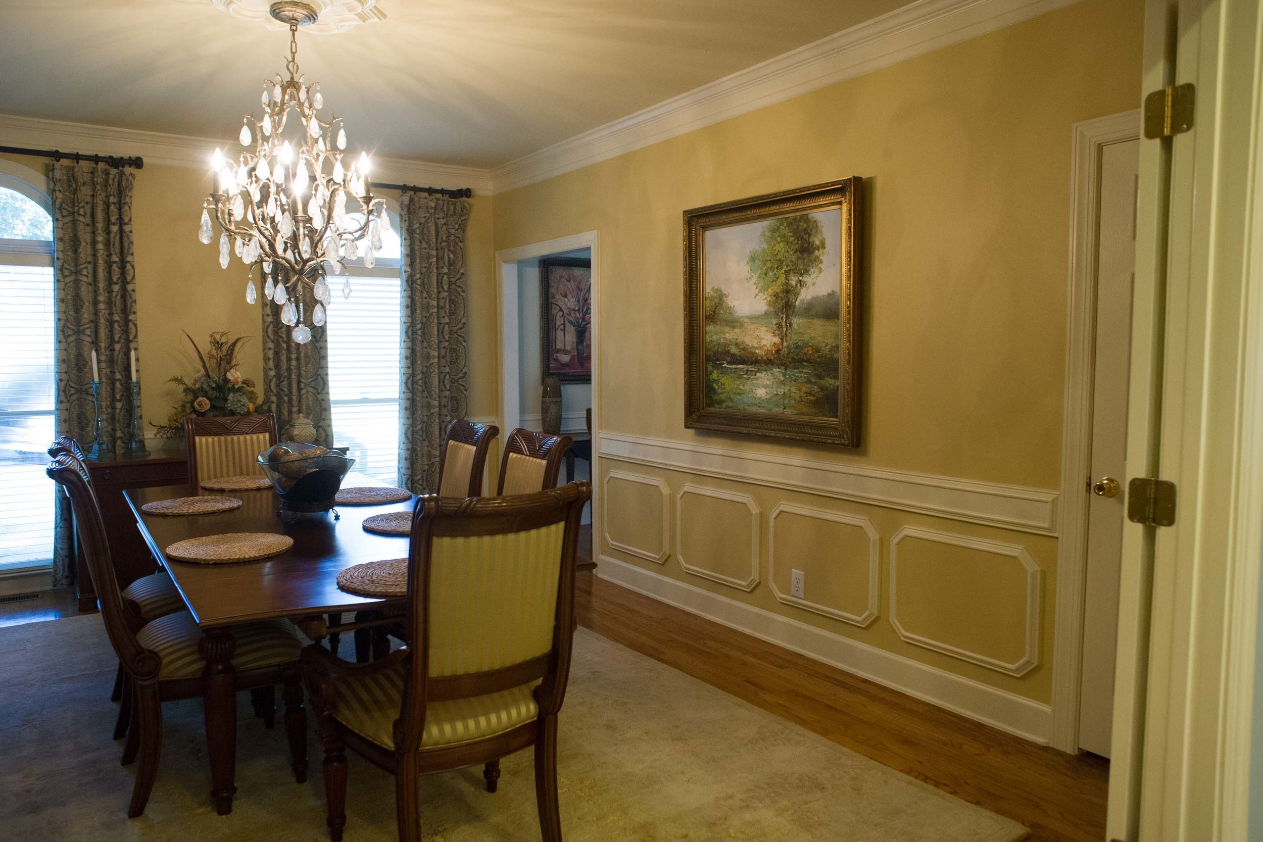 Dining room with wooden table, chairs, hardwood floor, chandelier and frame on the wall
