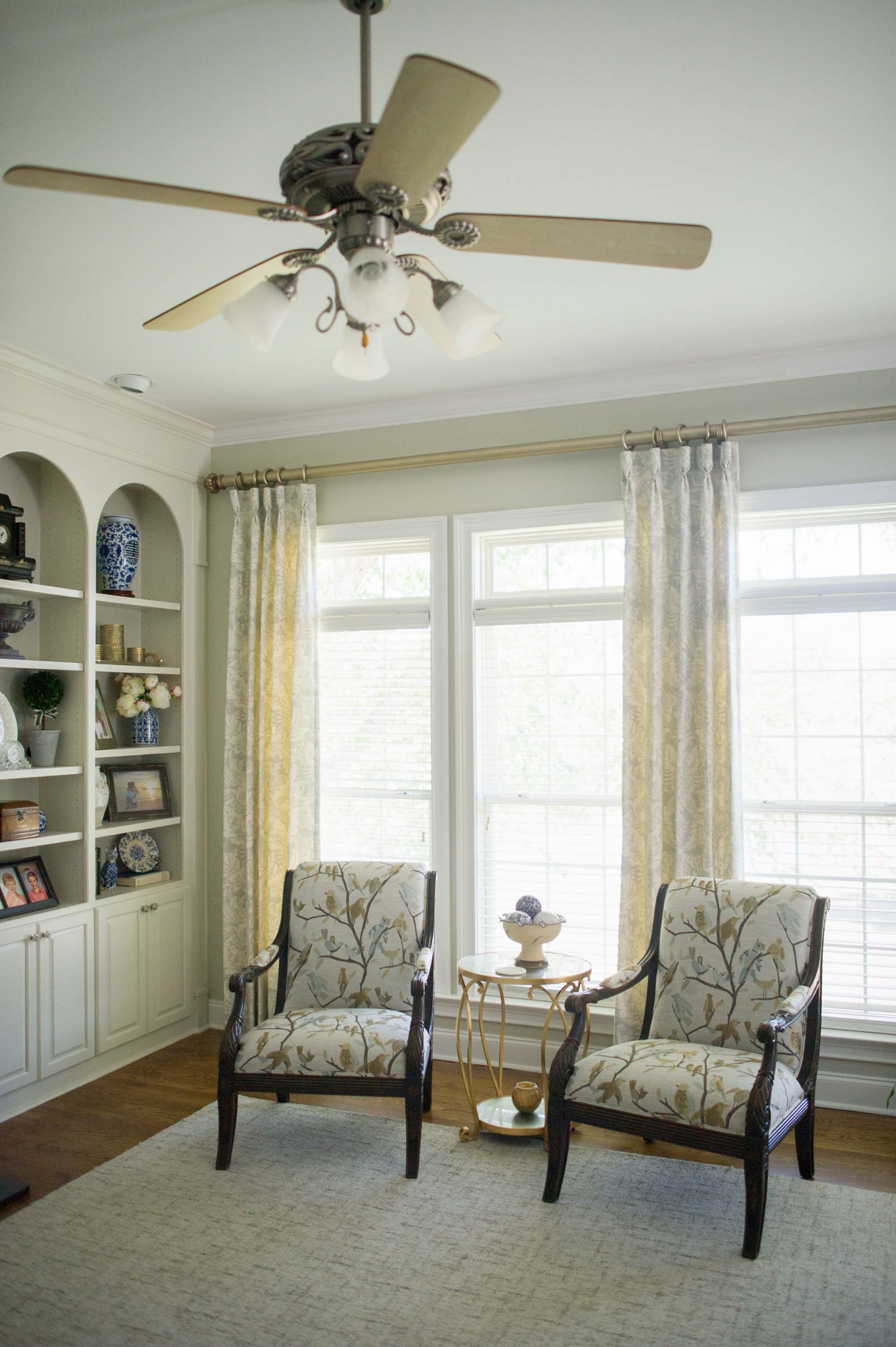 House interior with arm chairs, white window, and ceiling fan